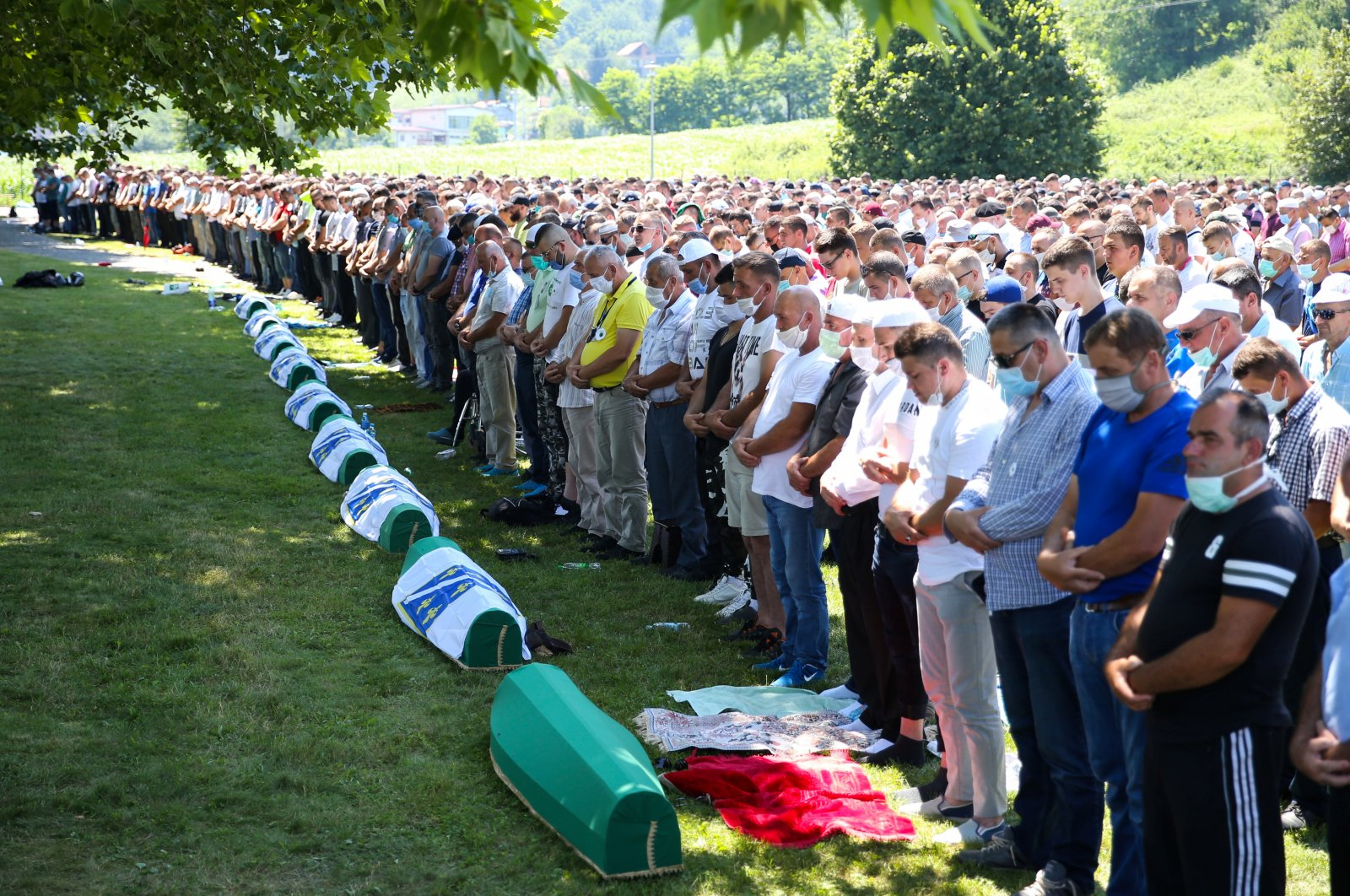 People pray near coffins at a graveyard during a mass funeral in Potocari near Srebrenica, Bosnia and Herzegovina on July 11, 2020. (Reuters Photo)