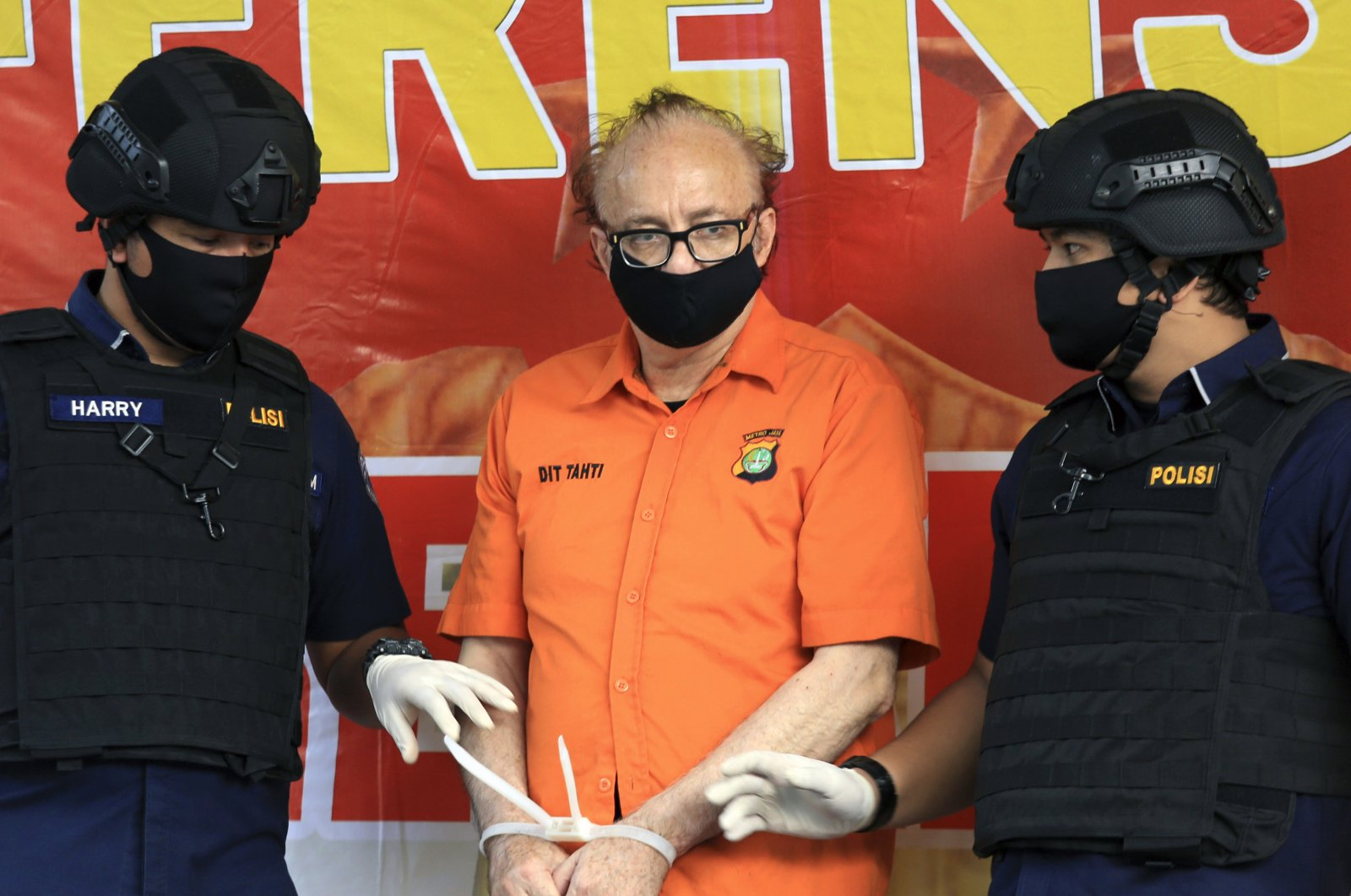 Police officers flank French national Francois Camille Abello, (C), as he is presented to the media during a press conference at the regional police headquarters in Jakarta, Indonesia, July 9, 2020. (AP Photo)