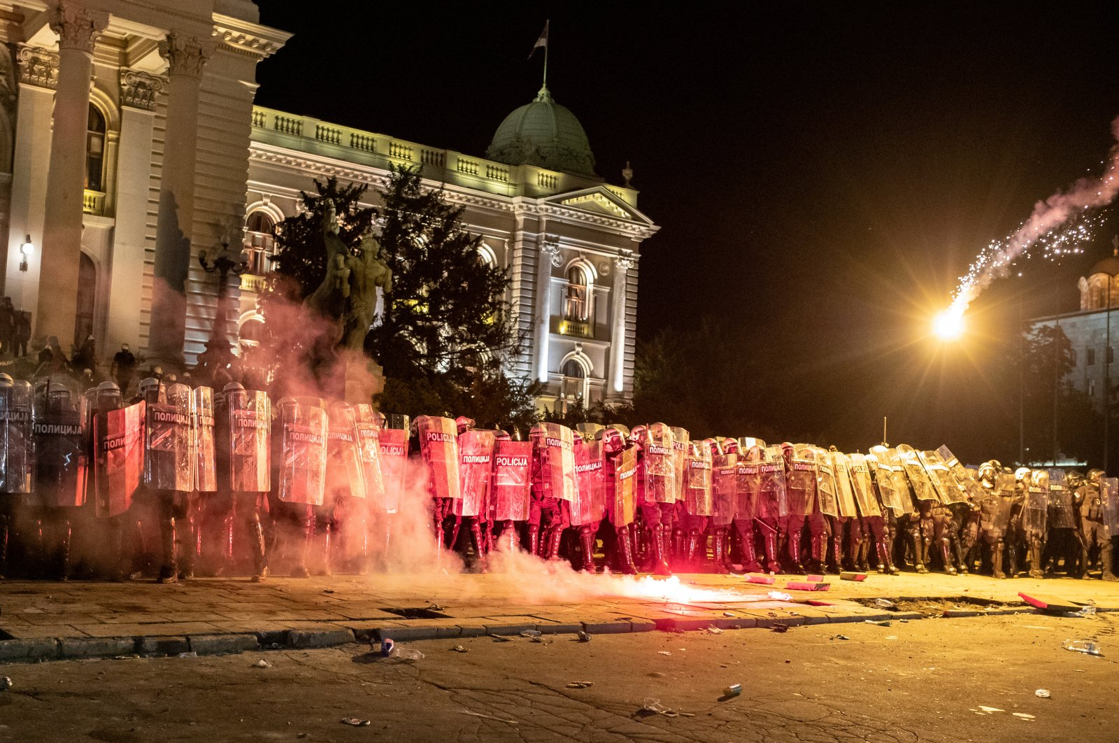 Demonstrators throw flares towards riot police at an anti-government protest amid the spread of the coronavirus disease (COVID-19), outside the parliament building in Belgrade, Serbia, July 10, 2020. (Reuters Photo)