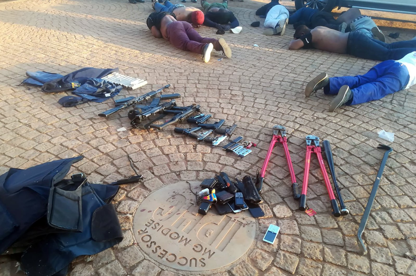 In this photo made available by the South African Police Services (SAPS), confiscated arms and ammunition, foreground, and arrested suspects, background, lay face-down at a church in Zuurbekom, near Johannesburg, Saturday, July 11, 2020. (AP Photo)