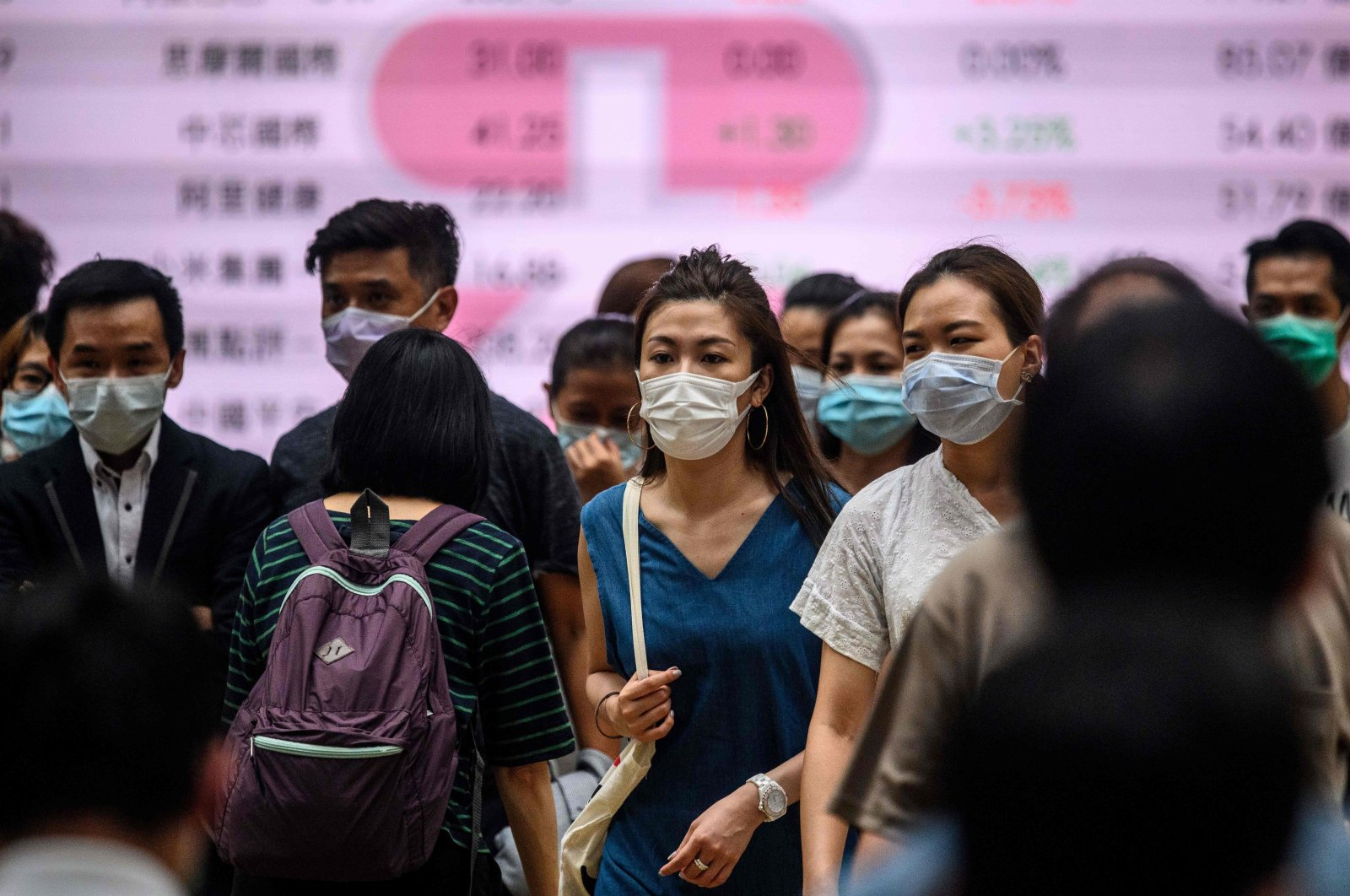 Pedestrians wear face masks as they cross a road in Hong Kong on July 10, 2020, as the city experiences new local outbreaks of the COVID-19 coronavirus. (AFP Photo)