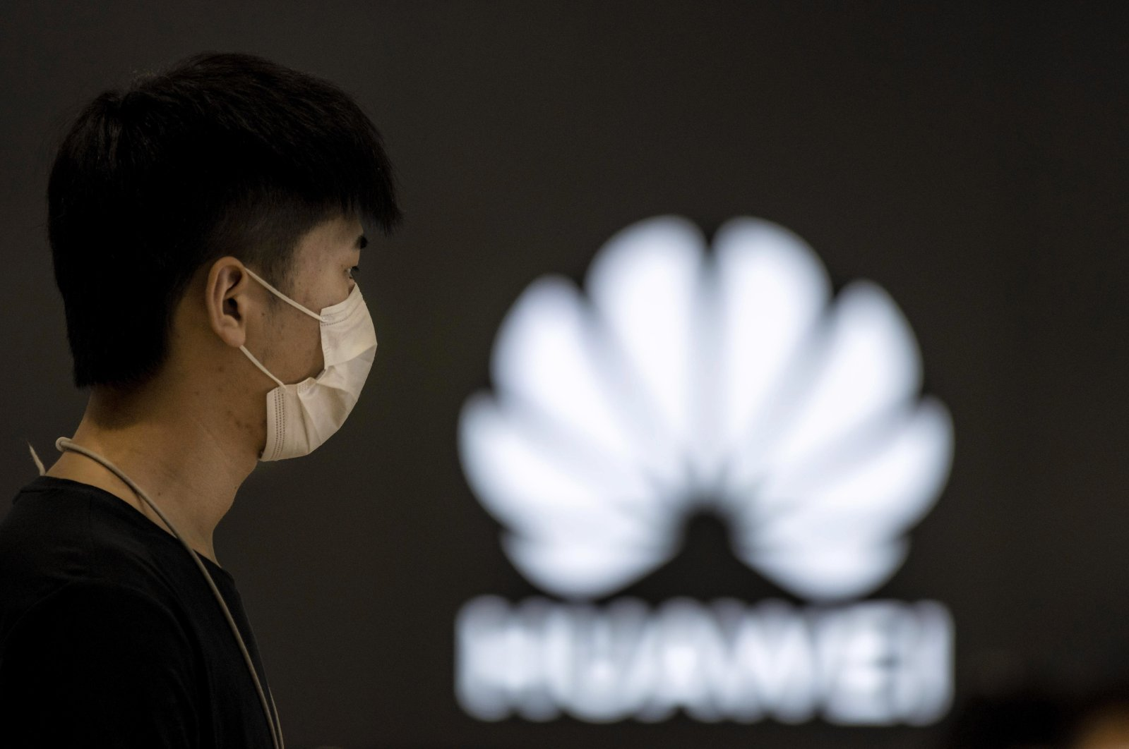 A man wearing a mask for protection, stands in a Huawei shop in Shanghai, China, July 6, 2020. (EPA Photo)