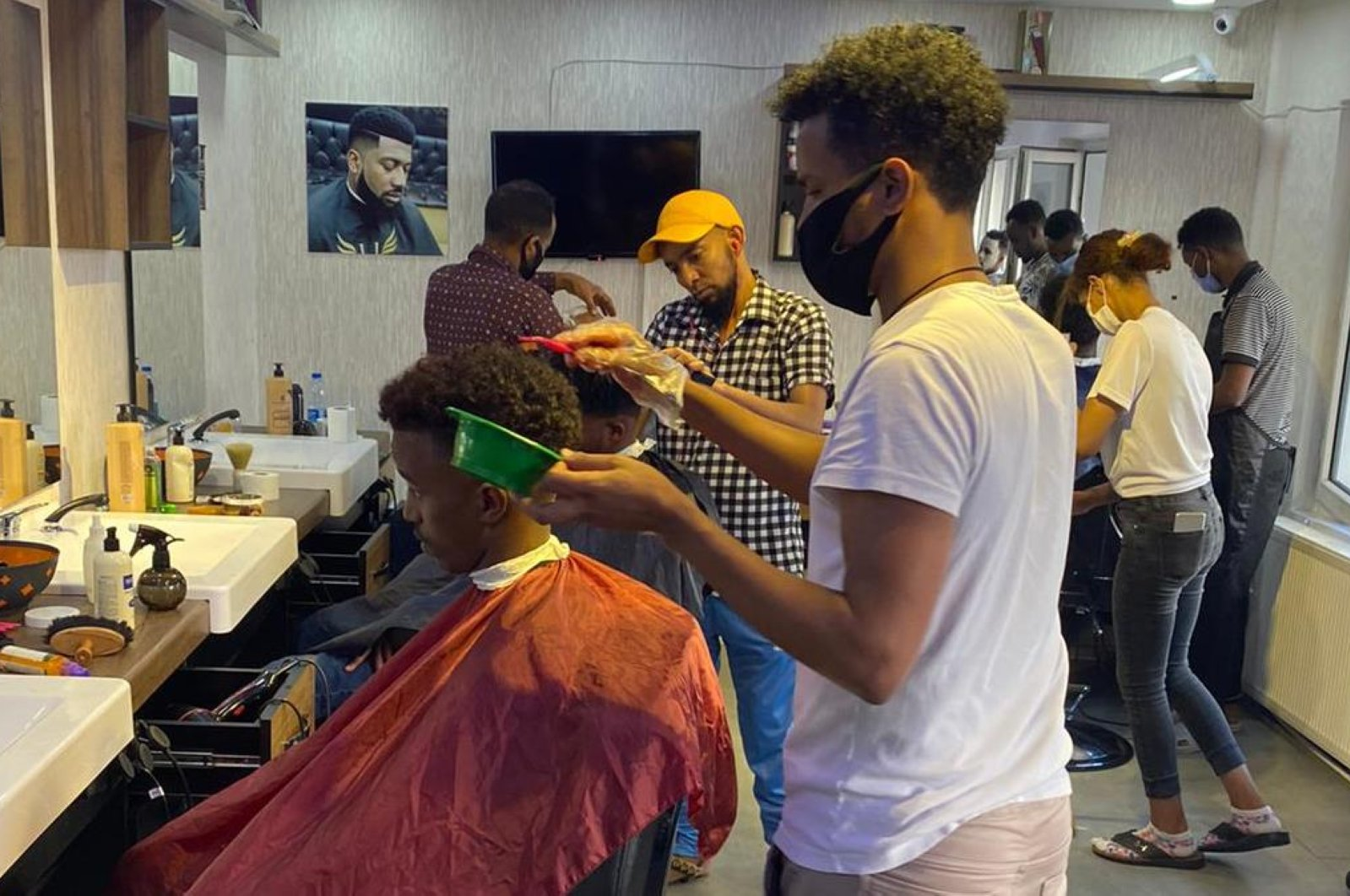 Jama brought in experienced barbers from several African countries to work at his shop in Ankara, Turkey. (AA Photo)