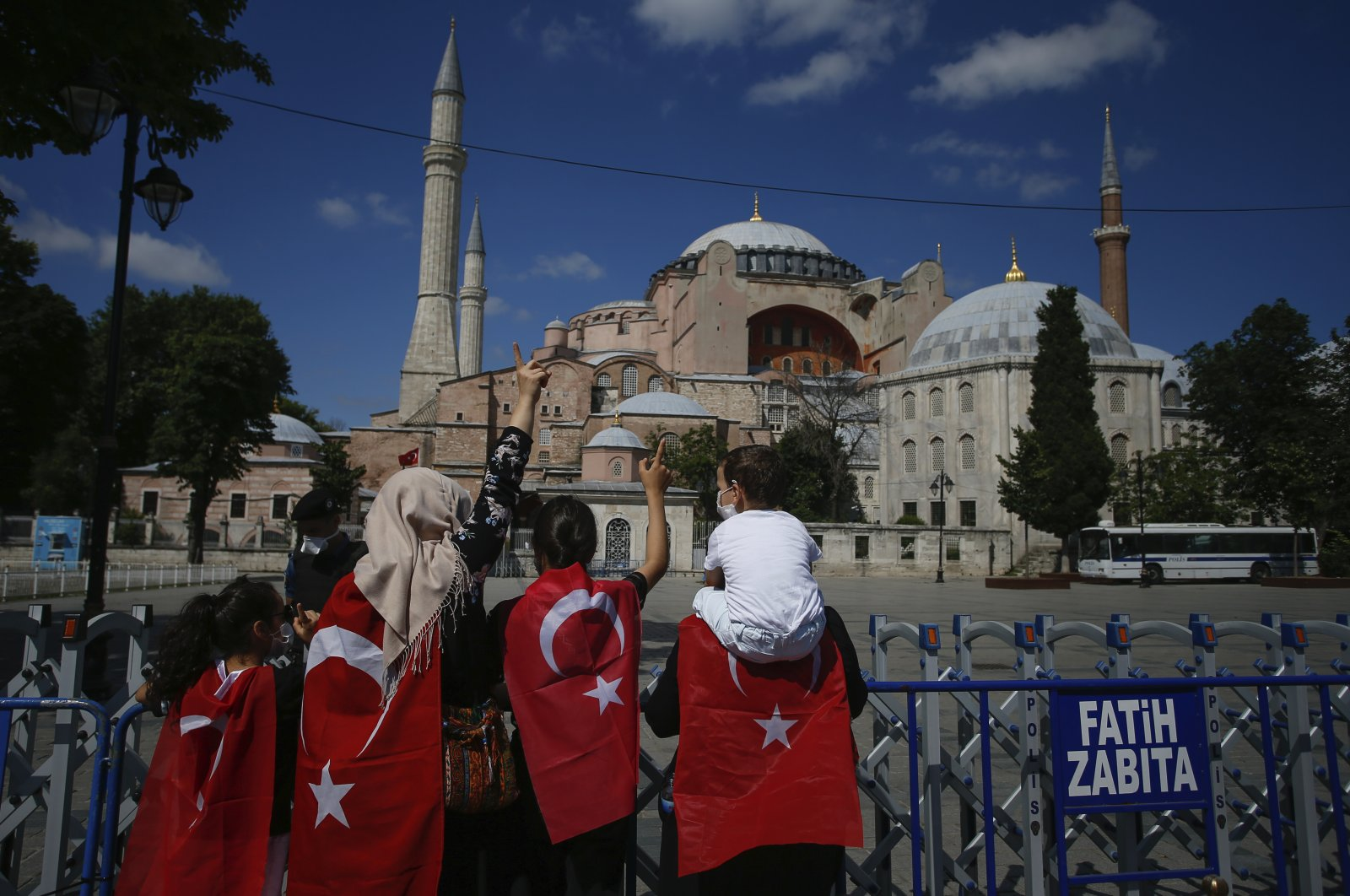 People, draped in Turkish flags stand outside the now closed Byzantine-era Hagia Sophia, one of Istanbul's main tourist attractions in the historic Sultanahmet district of Istanbul, July 11, 2020. (AP)
