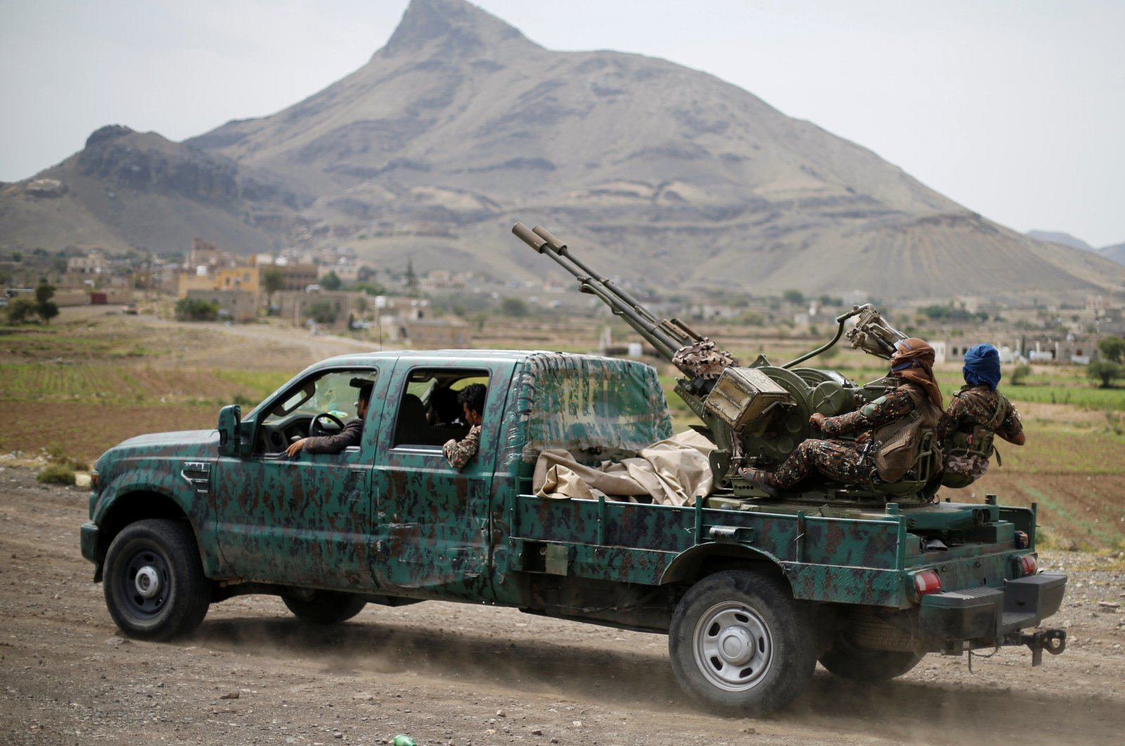 Houthi fighters man a machine gun mounted on a military truck as they parade during a gathering of Houthi loyalists on the outskirts of Sanaa, Yemen July 8, 2020. (Reuters Photo)
