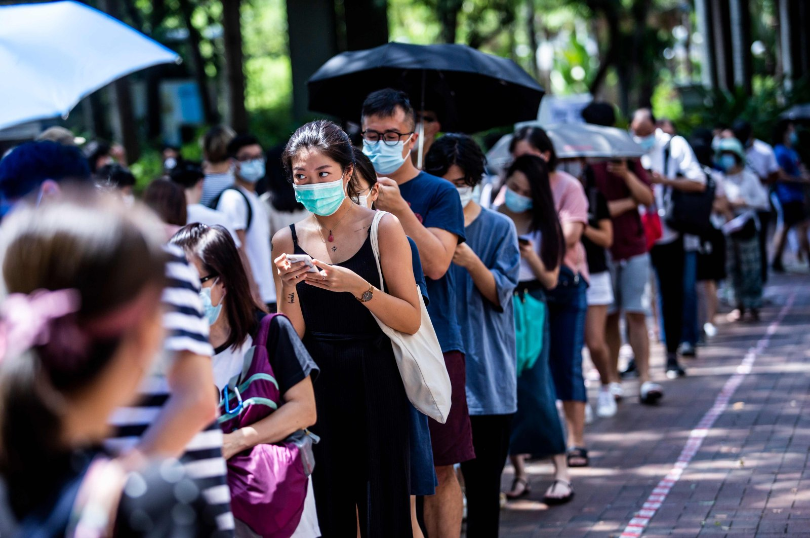 A woman (centre L) uses her phone while waiting to vote during primary elections in Hong Kong on July 12, 2020. (AFP Photo)