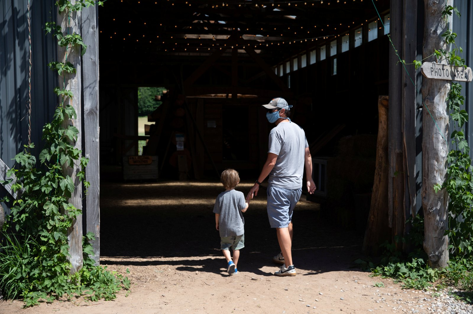 A man wearing a face mask walks with a child around Pond Hill Farm in Harbor Springs, Michigan, U.S. July 11, 2020. (Reuters Photo)