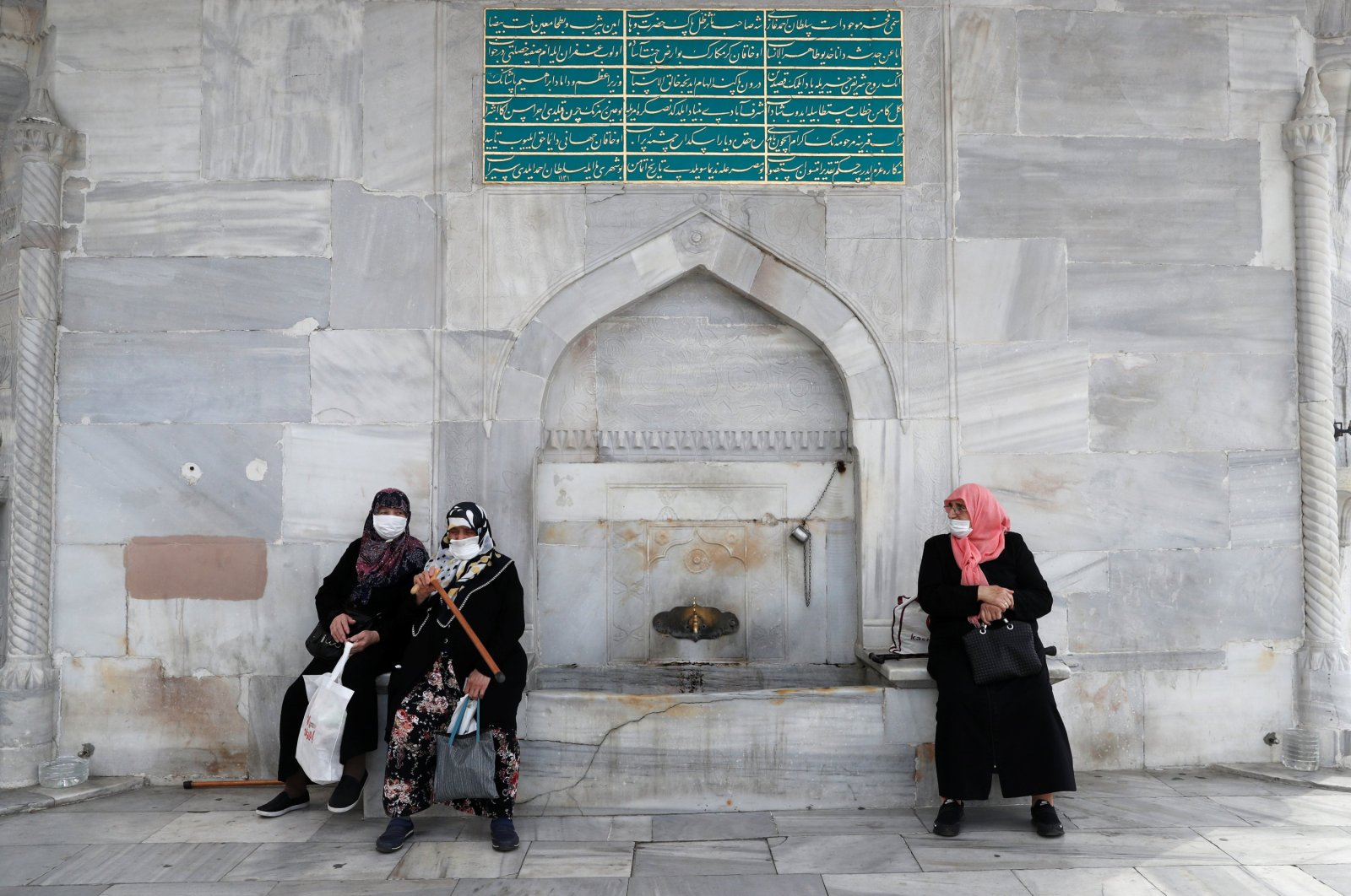 Women wearing protective face masks sit at an old fountain, amid the spread of COVID-19, in Istanbul, Turkey, July 9, 2020. (Reuters Photo)