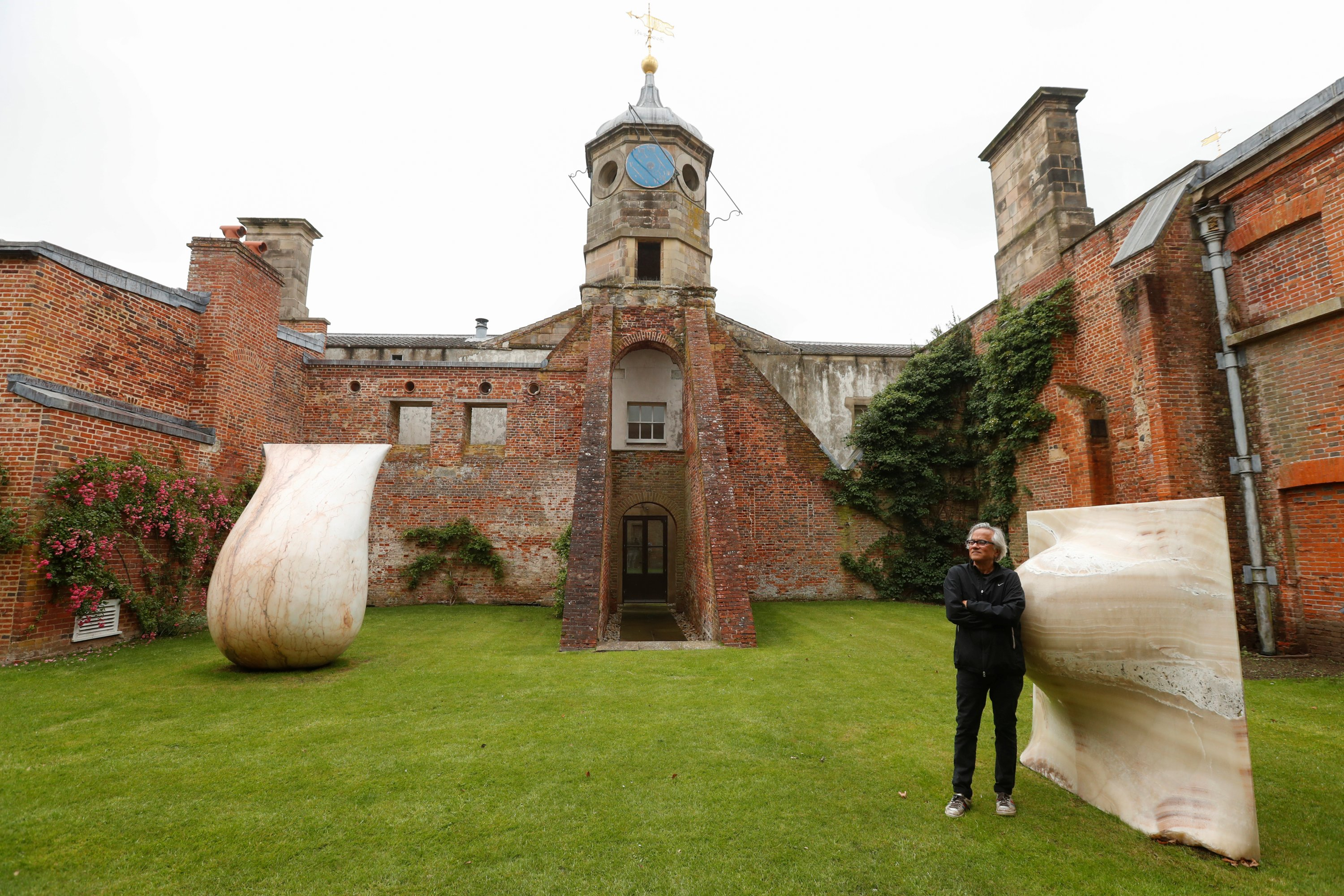 British-Indian artist Anish Kapoor poses with his sculptures in the gardens at Houghton Hall in Norfolk, Britain, July 9, 2020. (REUTERS PHOTO)