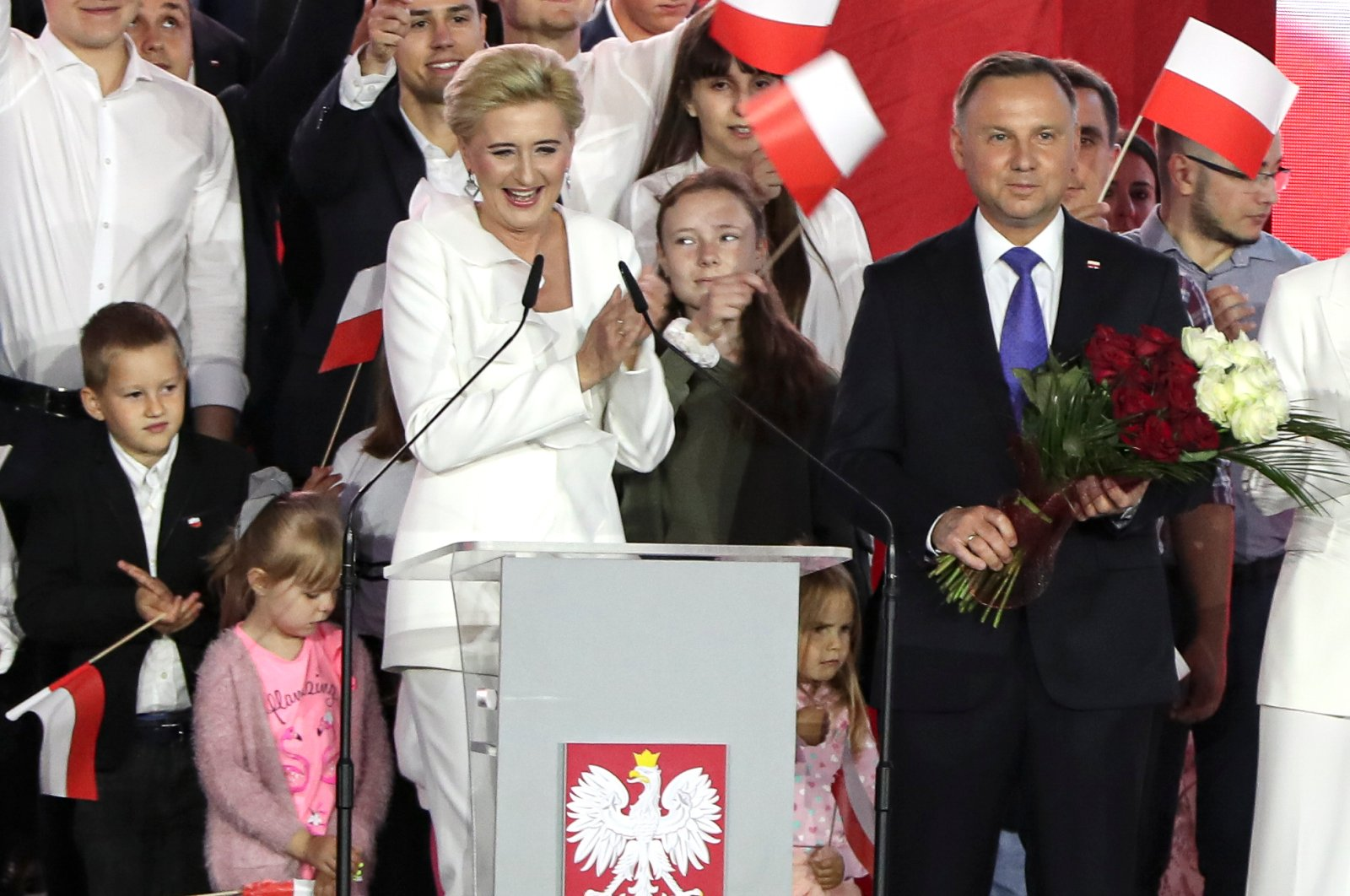 Incumbent President Andrzej Duda and his wife Agata Kornhauser-Duda smile after receiving flowers from supporters in Pultusk, Poland, July 12, 2020. (AP Photo)