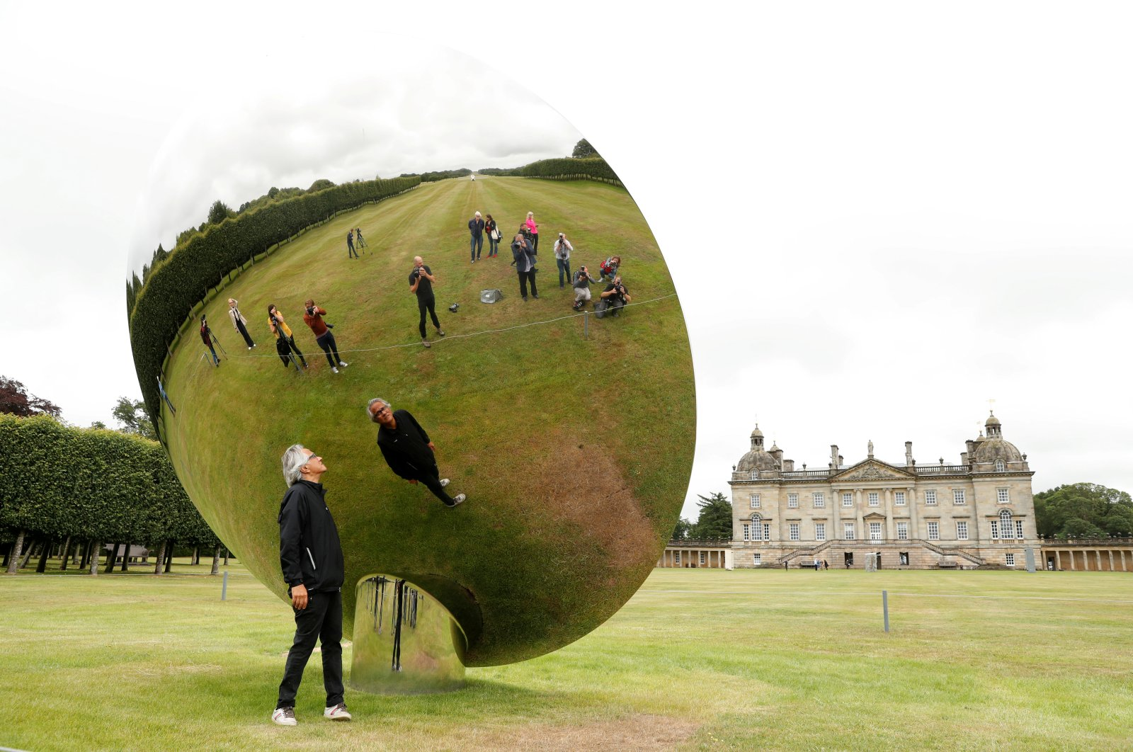 British-Indian artist Anish Kapoor is reflected in one of his sculptures as he poses for photographs in the gardens at Houghton Hall in Norfolk, Britain, July 9, 2020. (REUTERS PHOTO)