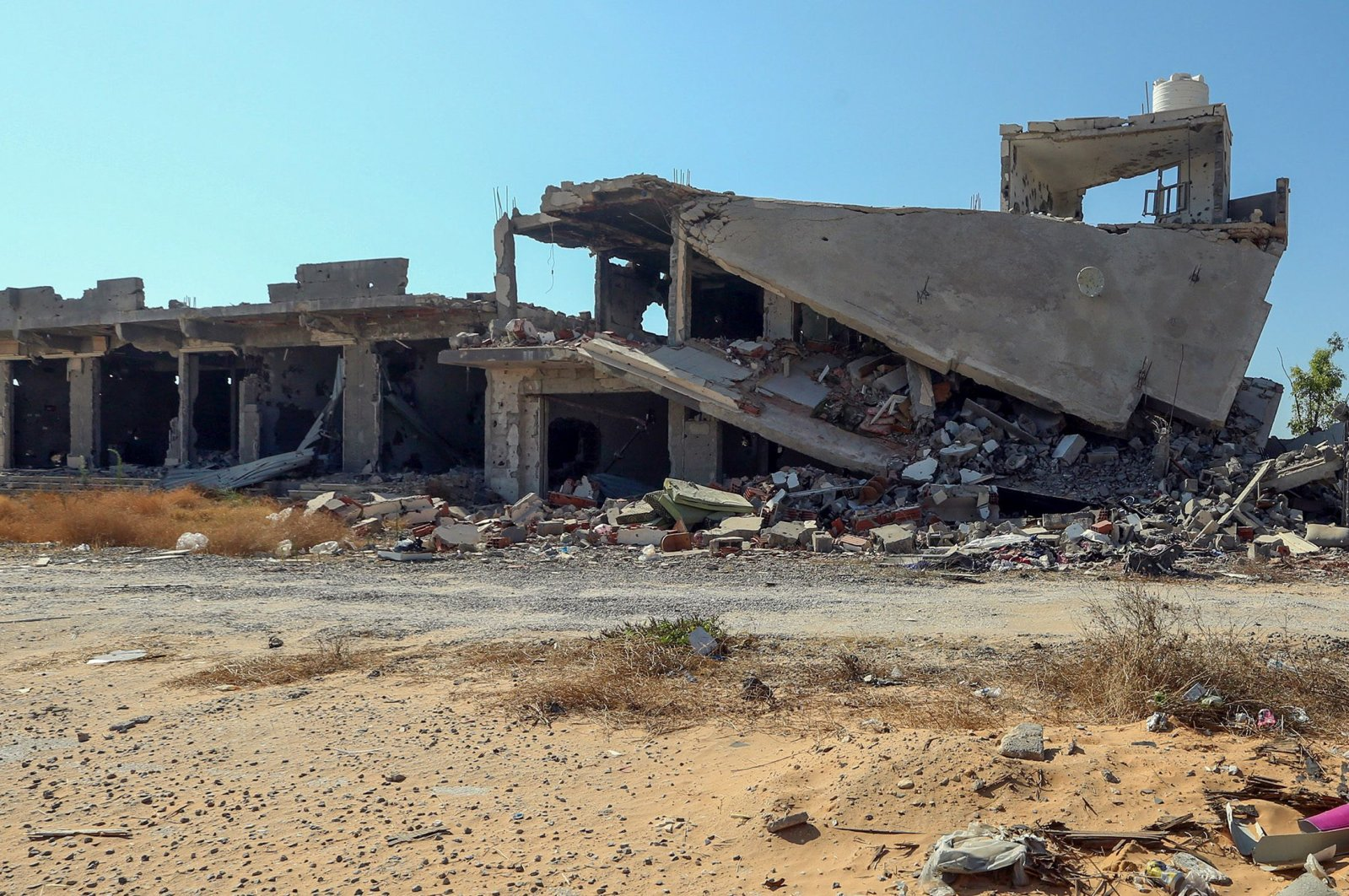 A picture shows a business, damaged during the 14 months of fighting between the UN-recognized Government of National Union (GNA) and putschist Gen. Khalifa Haftar, in a southern neighbourhood in the capital Tripoli, July 9, 2020. (AFP)