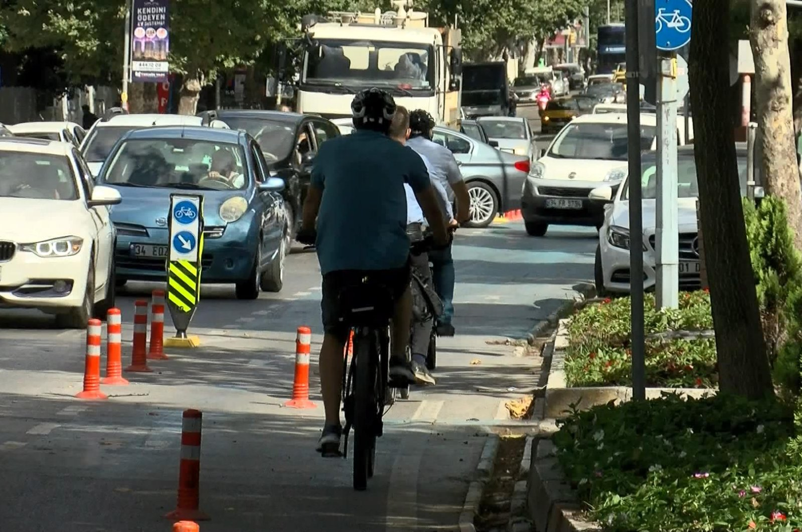 Cyclists in Istanbul use a bike lane that is blocked by a parked car, July 13, 2020. (DHA Photo)
