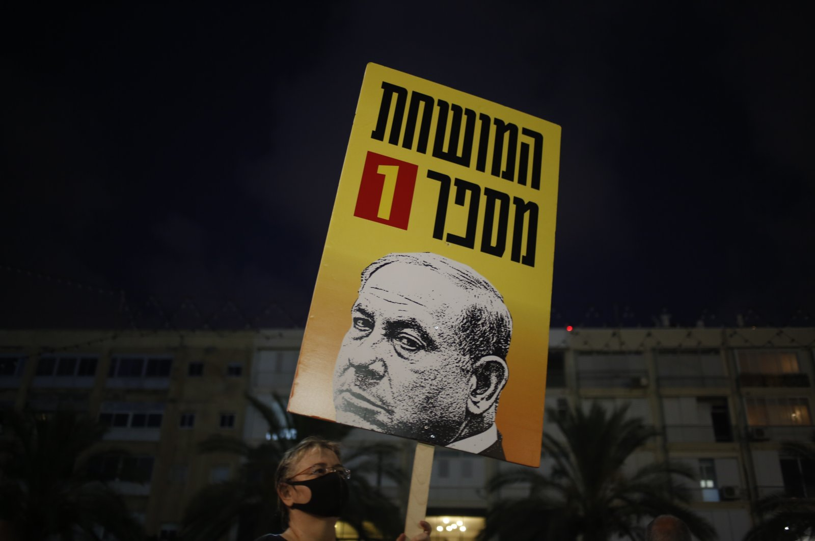 Protesters hold signs during a demonstration against Israel's government in Rabin Square, Tel Aviv, July 11, 2020. (AP Photo)