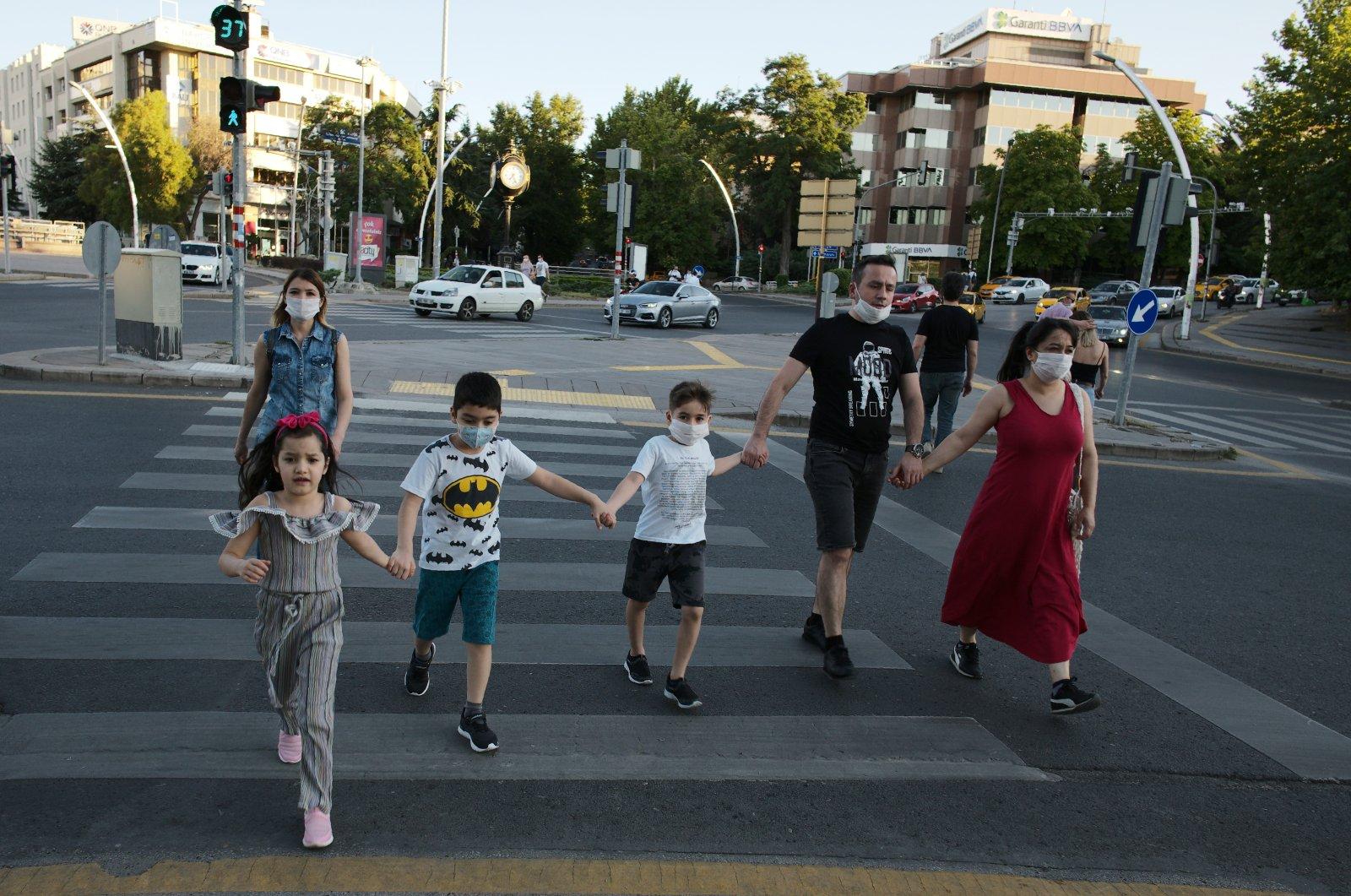 People wearing face masks cross a street in Ankara, Turkey, July 11, 2020. (AP Photo)