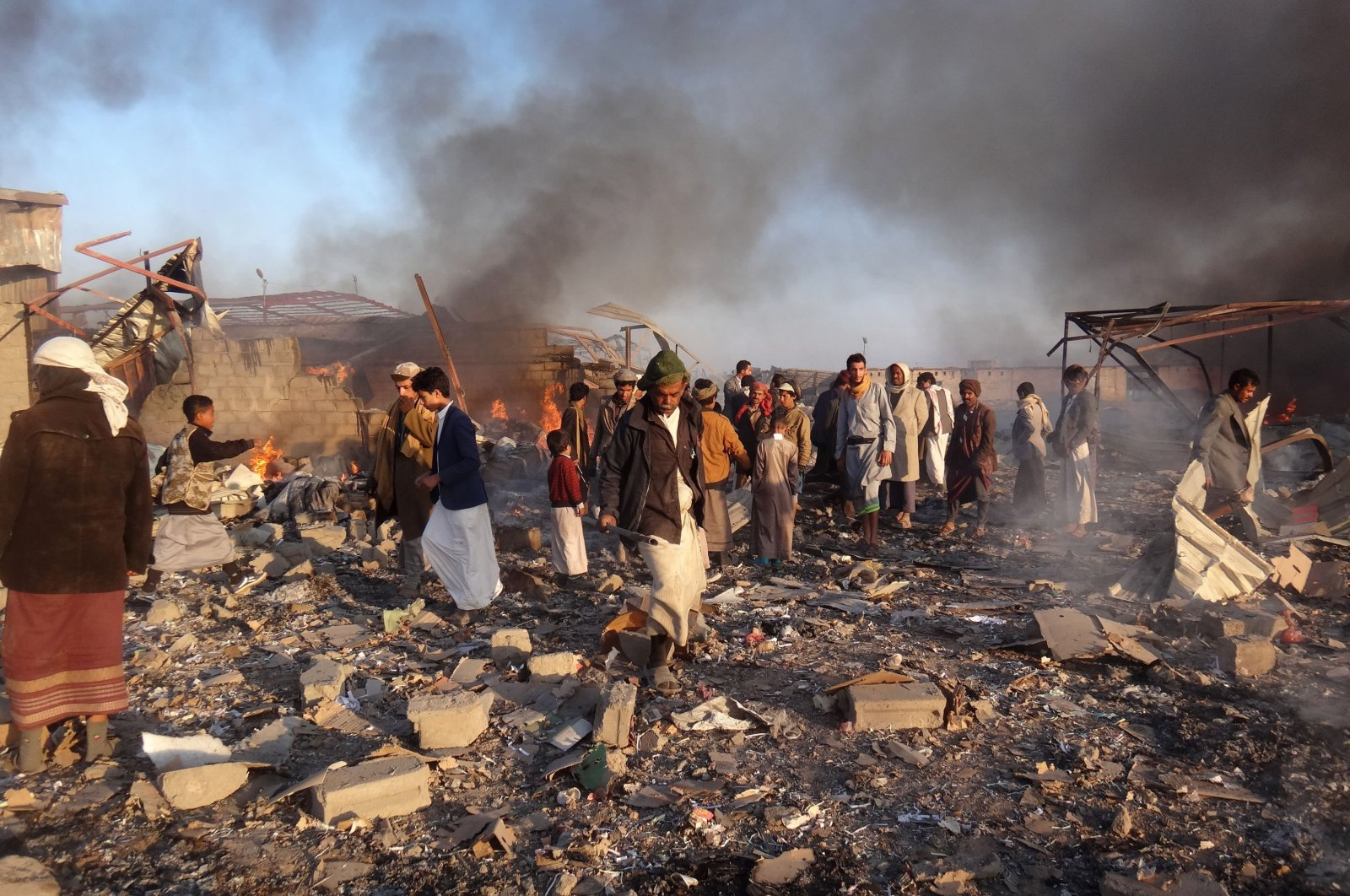 In this file photo, smoke rises as Yemenis inspect the damage at the site of airstrikes in the northwestern Houthi-held city of Saada, Yemen, Jan. 6, 2018. (AFP Photo)