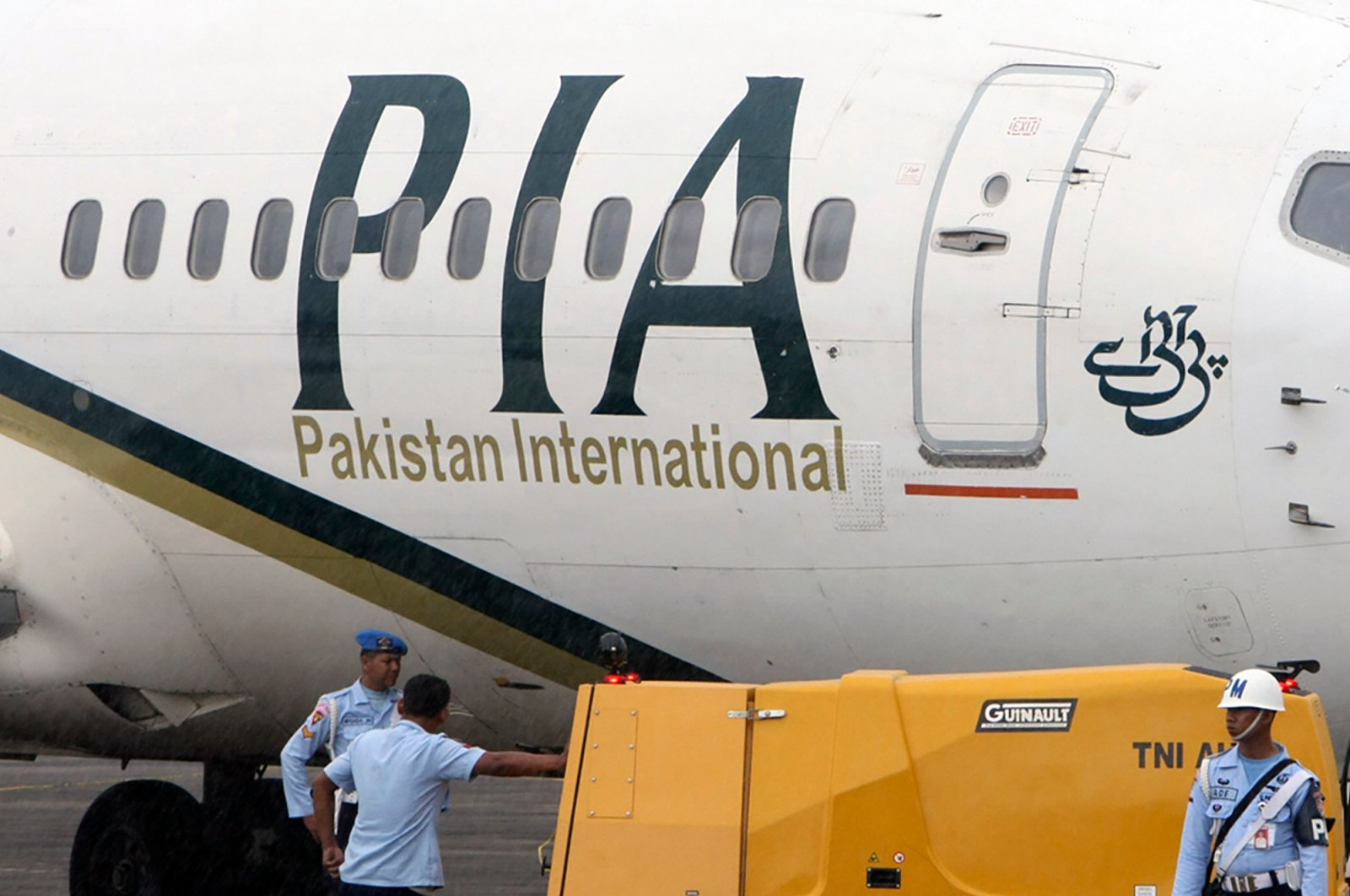 A Pakistan International Airlines passenger jet is parked on the tarmac at a military base in Makassar, Indonesia, March 7, 2011. (AP Photo)