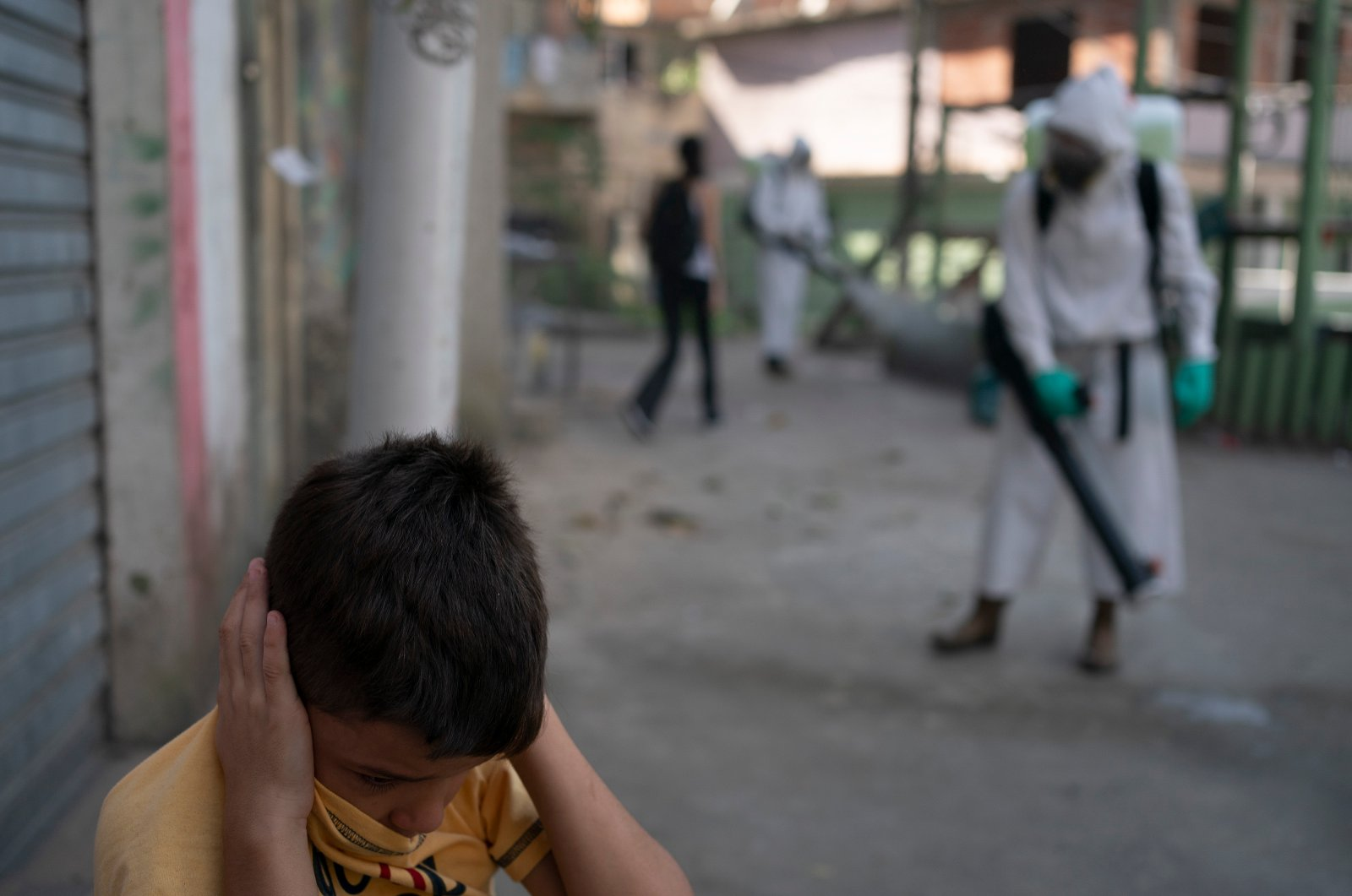 A boy protects his ears as a volunteer sprays disinfectant in an alleyway to help contain the spread of the coronavirus in the Babilonia slum of Rio de Janeiro, Brazil, July 12, 2020. (AP Photo)
