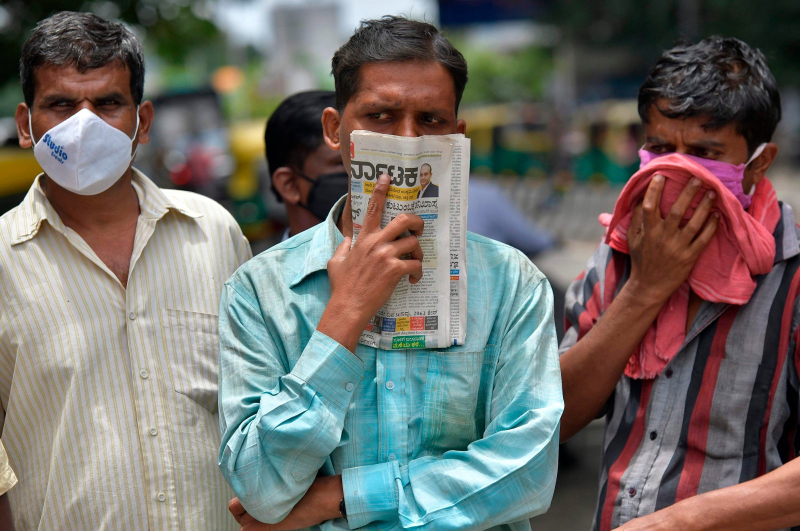 A man holds a newspaper to cover his face in the absence of his face mask during the coronavirus pandemic, in Bangalore, India, July 9, 2020. (AFP Photo)