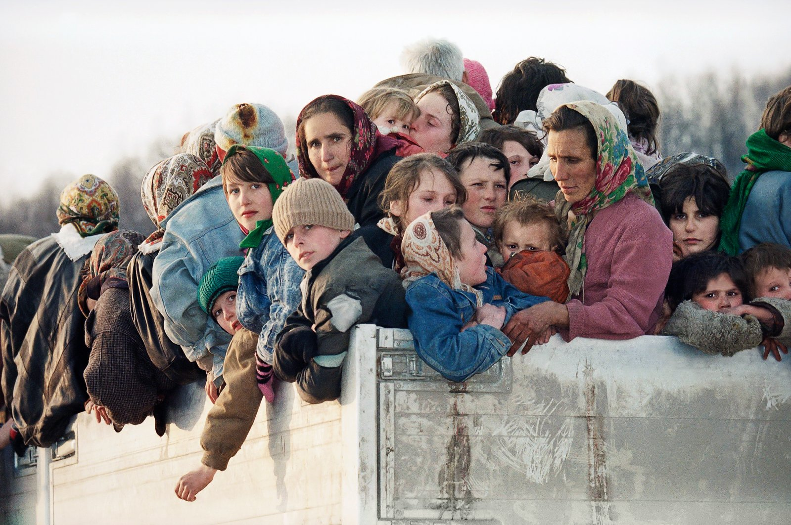 Evacuees from the besieged Muslim enclave of Srebrenica, packed on a truck en route to Bosnian city of Tuzla, pass through the Tojsici village, March 29, 1993. (AP Photo)