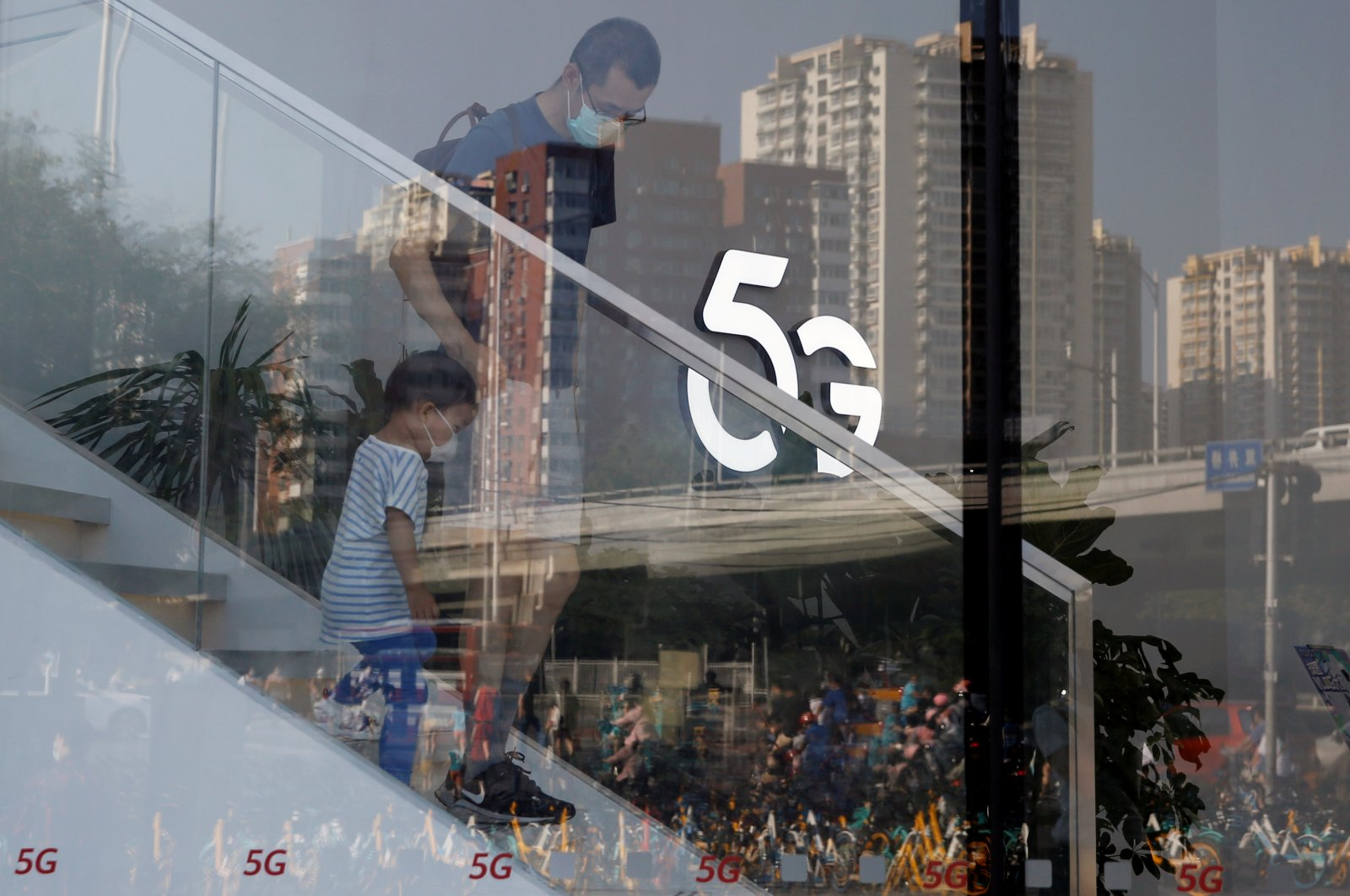 A man and a child wearing face masks walk past a 5G sign inside a Huawei store at a shopping mall in Beijing, China, July 14, 2020. (REUTERS Photo)
