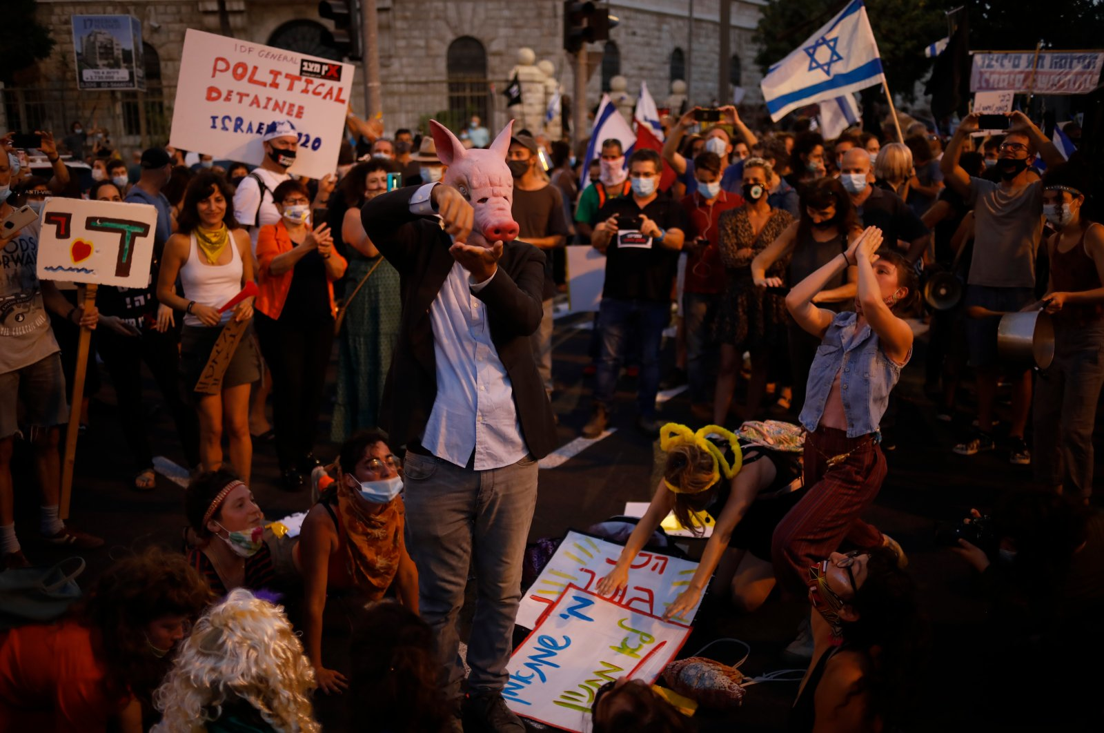 Demonstrators, defying orders to maintain social distancing requirements, chant slogans and blow horns outside Prime Minister's residence in Jerusalem, July 14, 2020. (AP Photo)