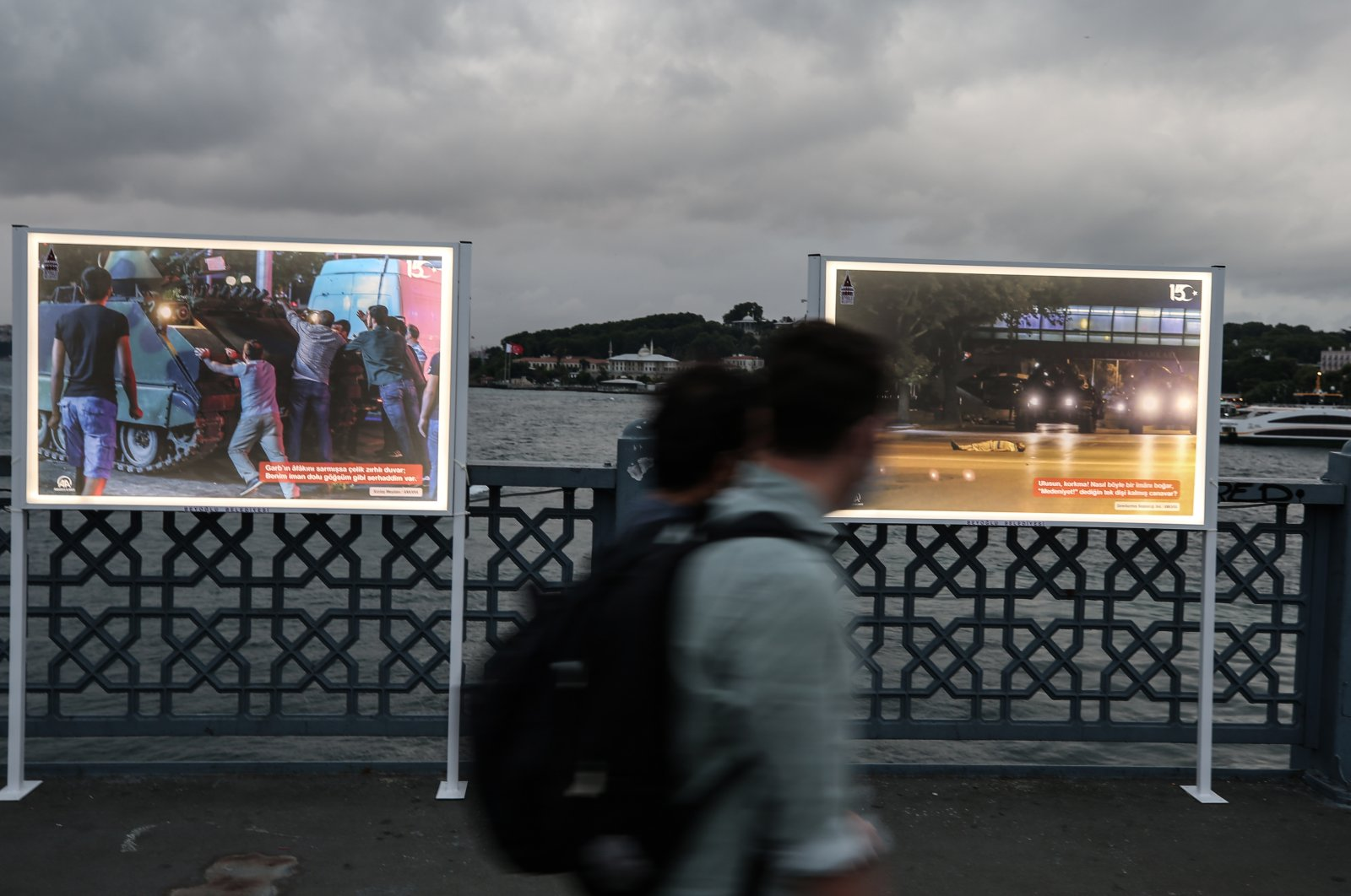 Pedestrians walk past a photo exhibition organized on Galata Bridge displaying the incidents and the people's resistance to the July 15 coup attempt by the Gülenist Terror Group (FETÖ), Istanbul, Turkey, July 13, 2020. (AA Photo)
