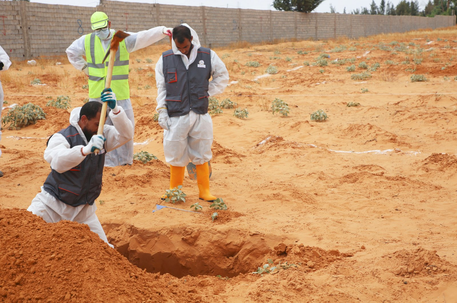 Libyan Ministry of Justice employees dig out at a site of a suspected mass grave in the town of Tarhouna, Libya, Tuesday, June 23, 2020. (AP Photo)