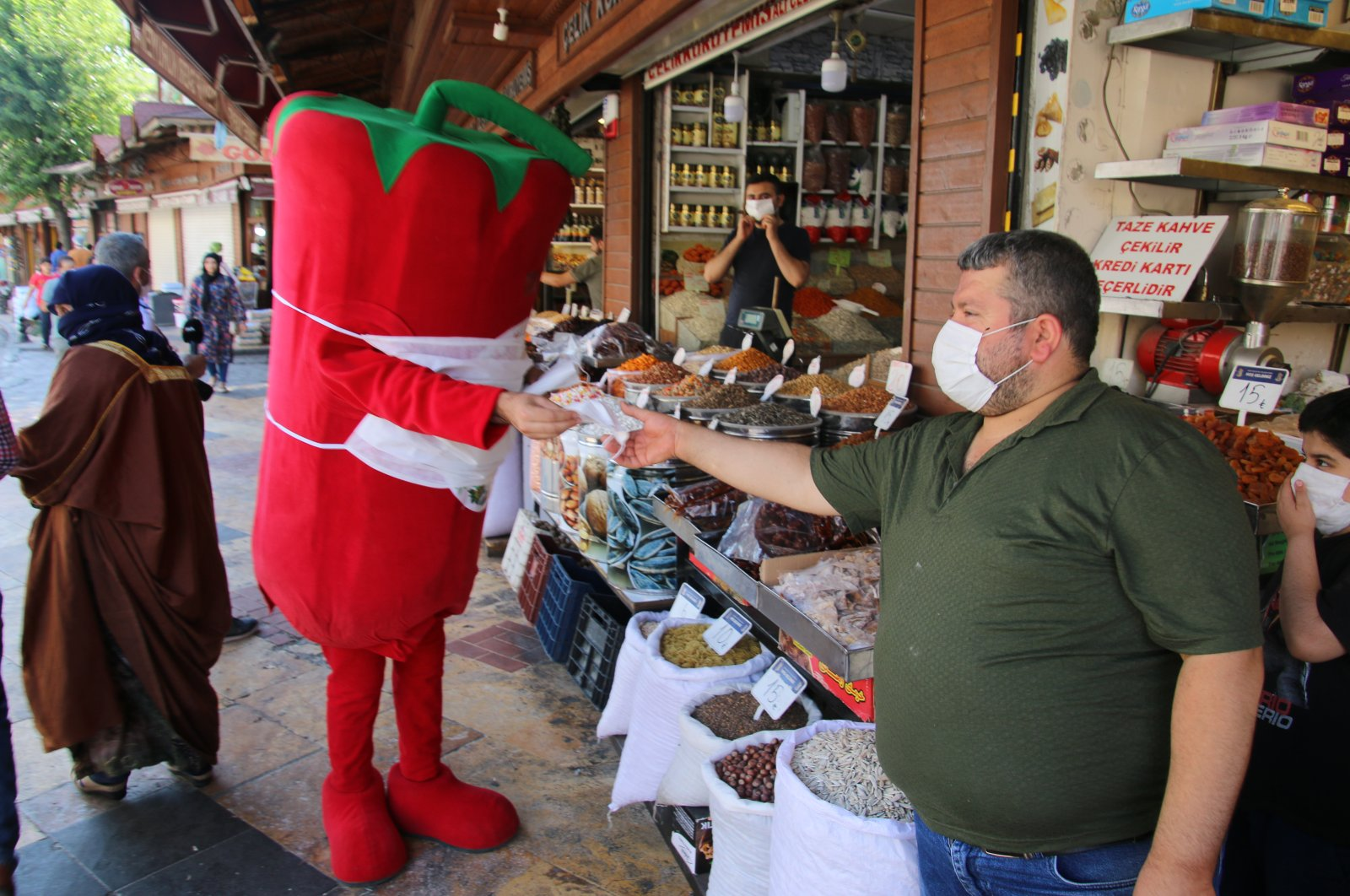 Dressed up as giant isot peppers, mascots distribute free masks to businesses and shop owners in Şanlıurfa, July 13, 2020. (AA Photo)