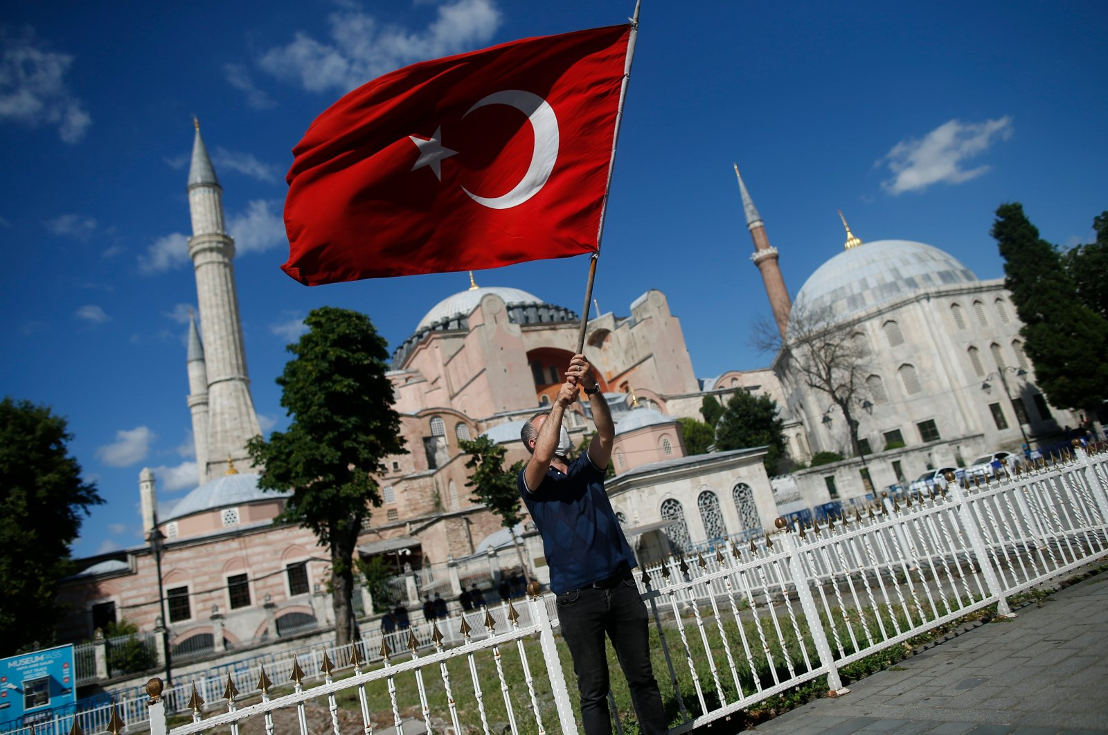 A man waves a Turkish flag outside the Byzantine-era Hagia Sophia, one of Istanbul's main tourist attractions in the historic Sultanahmet district of Istanbul, following Turkey's Council of State's decision, July 10, 2020. (AP)