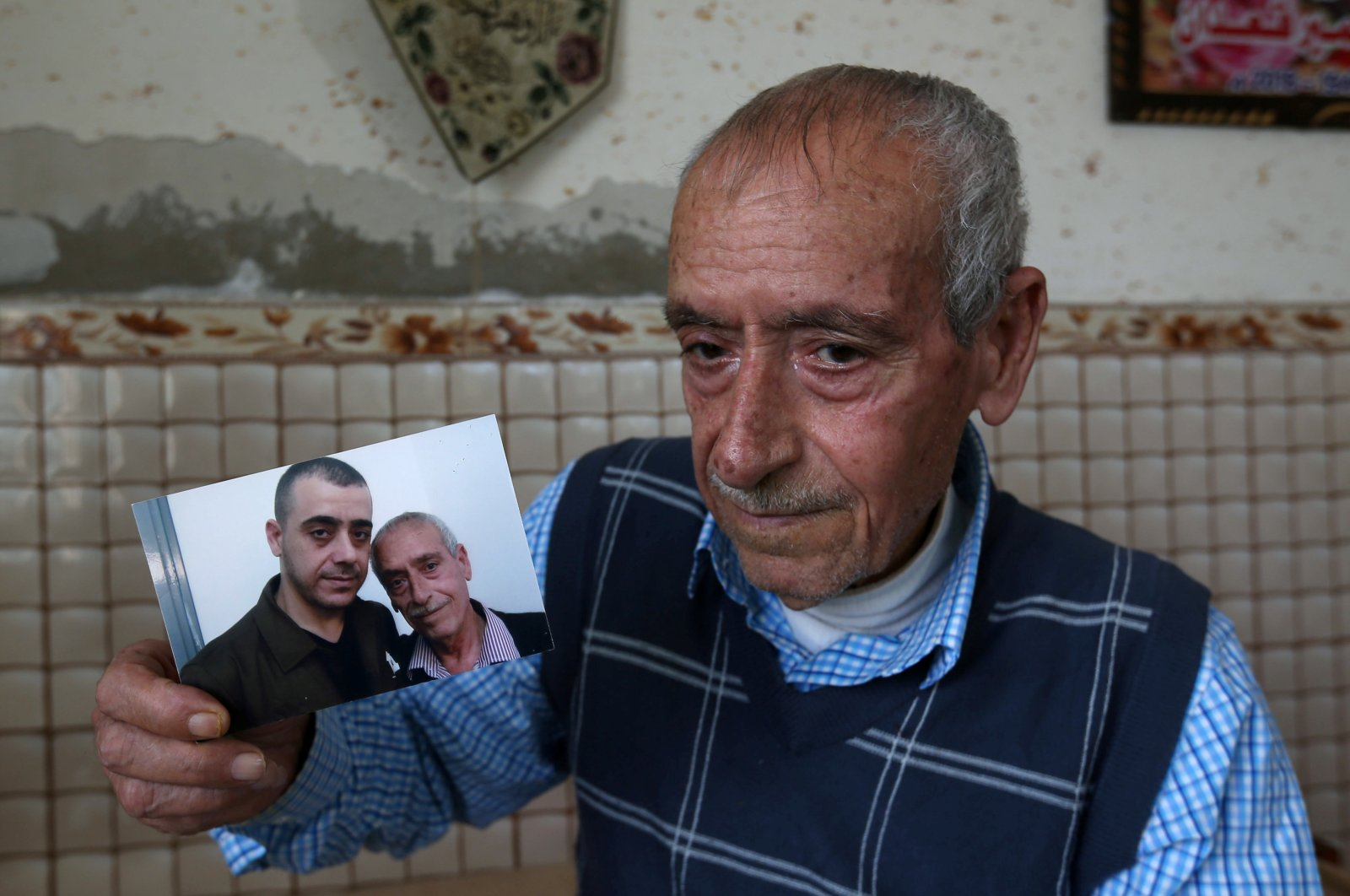 Palestinian man Sameeh Qe'dan, who marks a calendar with a cross to count down the days until his son Abdel-Raouf is released from an Israeli jail, shows a picture of him with Abdel-Raouf, in his home in Rafah in the southern Gaza Strip July 14, 2020. (Reuters Photo)