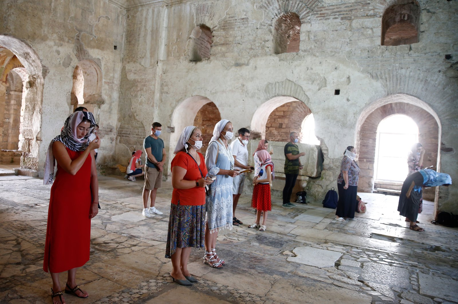 People wearing face masks against COVID-19 pray at an ancient church in Antalya, Turkey, July 14, 2020. (AA Photo)