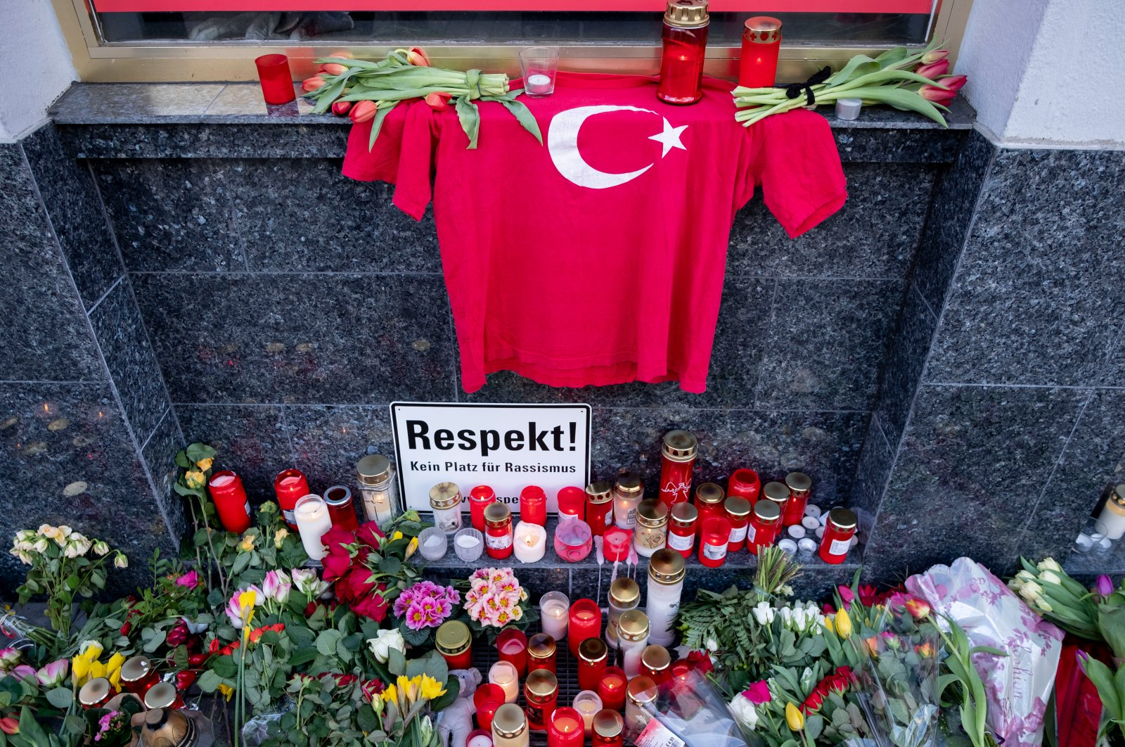 Flowers, candles and a Turkish jersey are laid near a bar in central Hanau, Germany, Feb. 22, 2020. (AP Photo)
