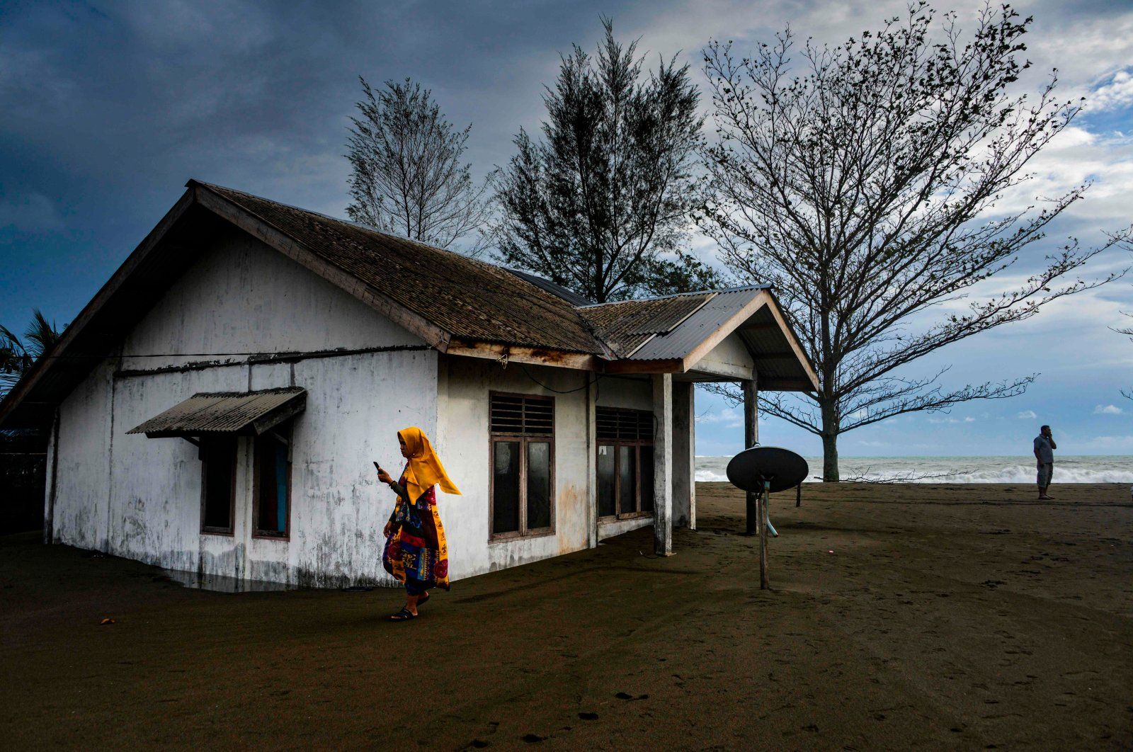 A resident walks past outside a house damaged by tidal waves at Meulaboh beach in Aceh province on July 12, 2020. (AFP Photo)