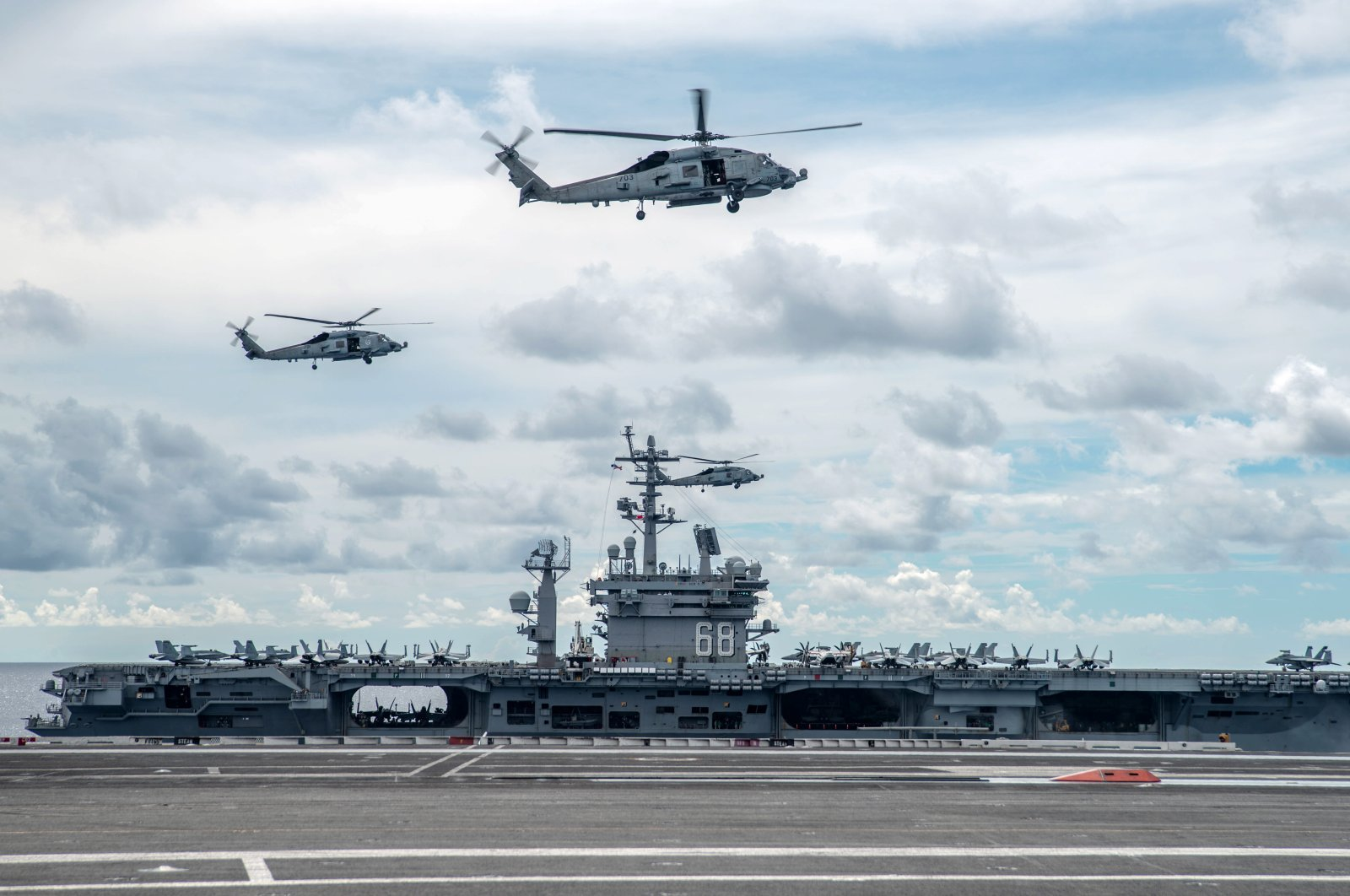 Two MH-60R Seahawks, attached to the Saberhawks of Helicopter Maritime Strike Squadron (HSM) 77, hover over the Navy's only forward-deployed aircraft carriers USS Ronald Reagan (CVN 76) and USS Nimitz (CVN 68), during a drill in the South China Sea, 06 July 2020. (EPA Photo)