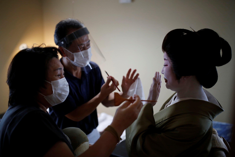 2020年6月29日,日本东京的jiutamai舞者Tokijyo Hanasaki上的化妆师Mitsunaga Kanda和假发设计师Yurie Hatanaka戴着防护口罩和面罩。