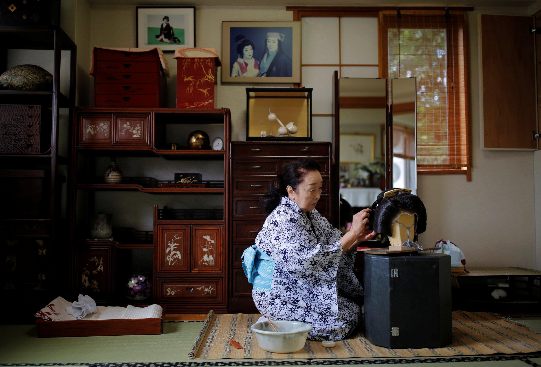 艺妓Ikuko于2020年6月23日在日本东京的冠状病毒爆发期间准备在豪华餐厅的顾客主持的聚会上工作时,在客厅里梳理假发。(路透社照片)