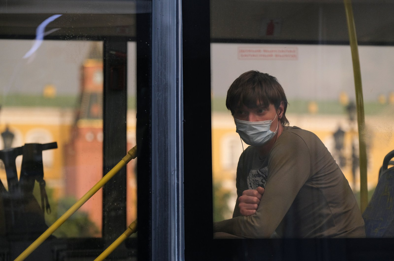 A passenger wearing a protective face mask as a preventive measure against COVID-19 looks through a bus window in Moscow, Russia, June 19, 2020. (REUTERS Photo)