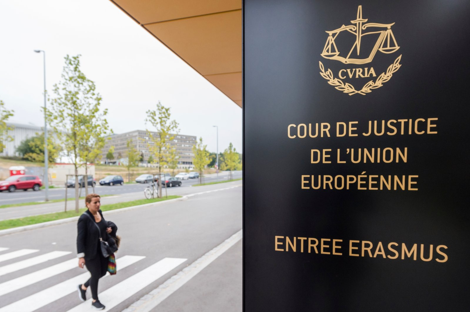 A woman walks by the entrance to the European Court of Justice (ECJ) in Luxembourg, Oct. 5, 2015. (AP Photo).