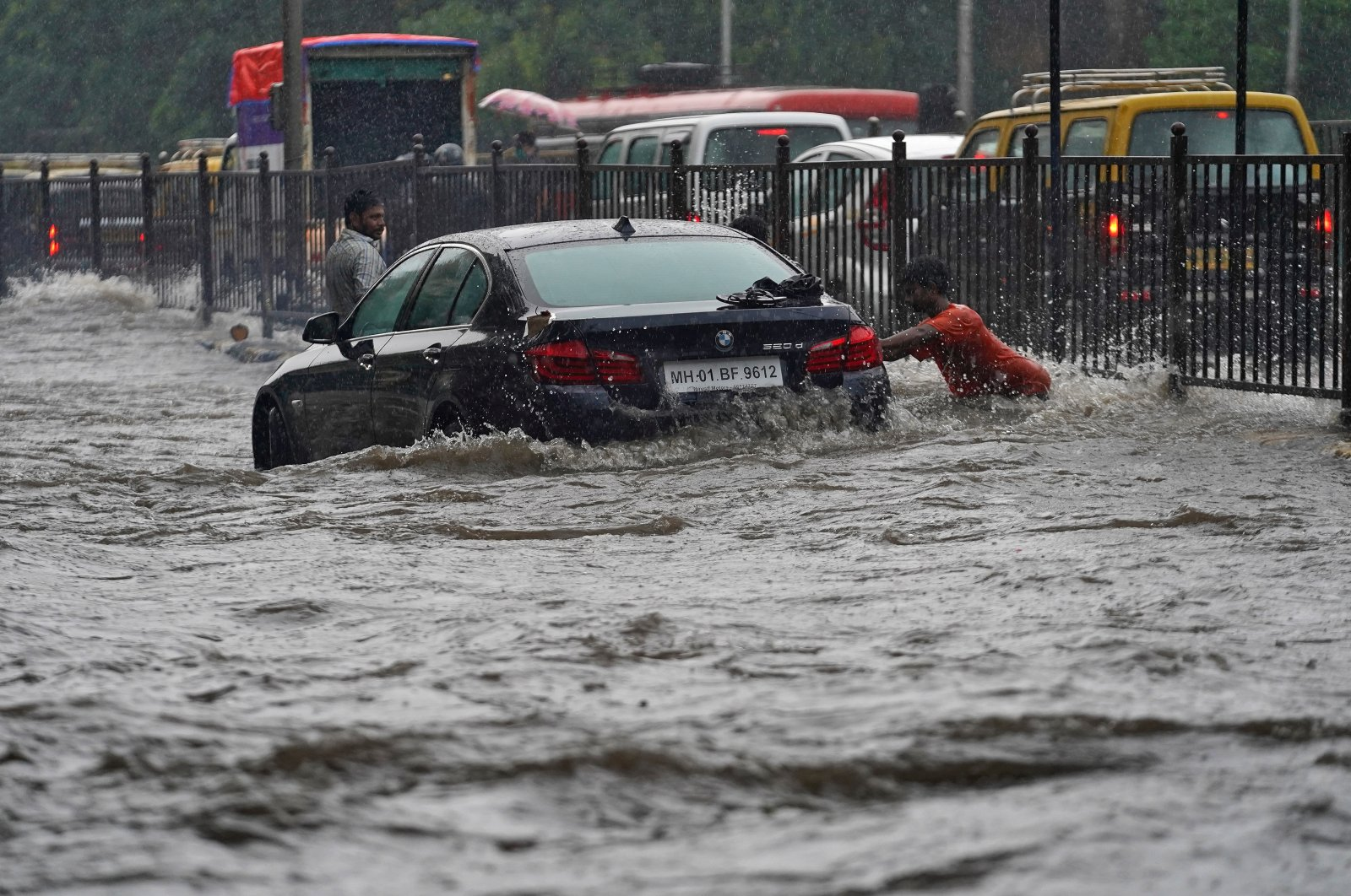 A man pushes a car, stuck in a flooded road, during heavy rains in Mumbai, India, July 4, 2020. (Reuters Photo)