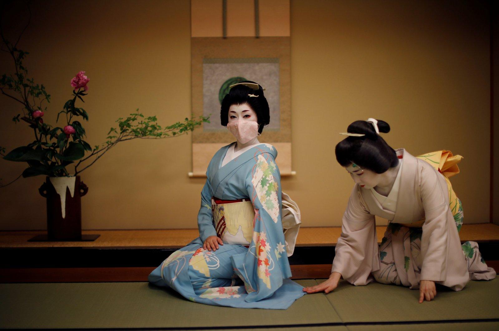 Mayu adjusts Koiku's kimono as Koiku wears a protective face mask to pose for a photograph at a luxury Japanese restaurant, Tokyo, Japan, June 23, 2020. (Reuters Photo)