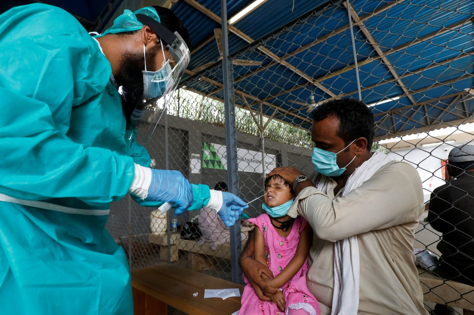A paramedic wearing protective gear takes a nasal swab from a child, to be tested for the coronavirus, in Karachi, Pakistan, July 13, 2020. (Reuters Photo)