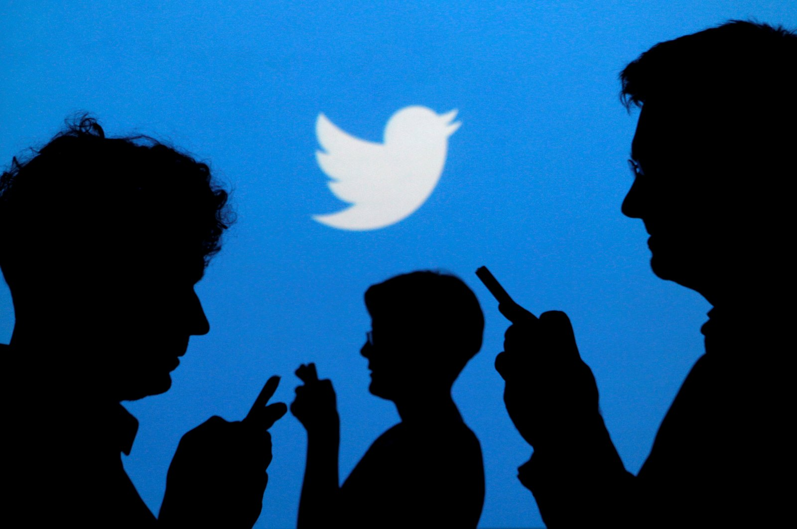 People holding mobile phones are silhouetted against a backdrop projected with the Twitter logo in this illustration picture taken in Warsaw, Poland, Sept. 27, 2013. (Reuters Photo)
