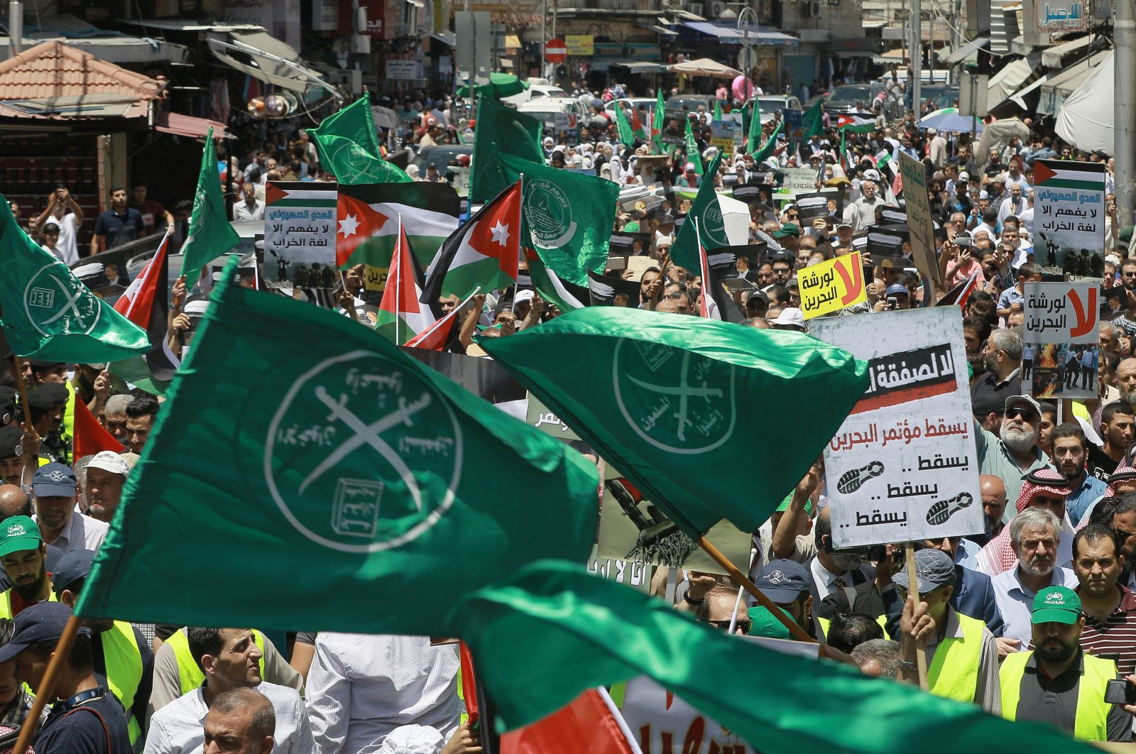 Jordanian flags, as well as flags of the Muslim Brotherhood and other political parties, are waved with other protest signs denouncing the U.S.-led Middle East economic conference in Bahrain, June 21, 2019. (AFP Photo)