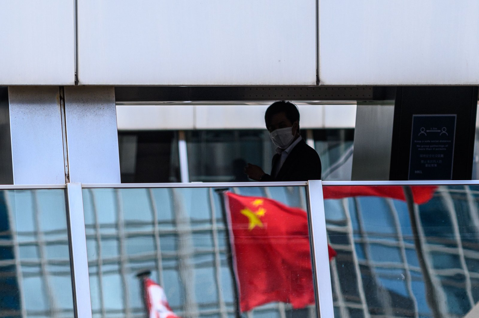 A man walks past a reflection of the Chinese flag (C) on a footbridge in the Central district of Hong Kong on July 16, 2020. (AFP Photo)