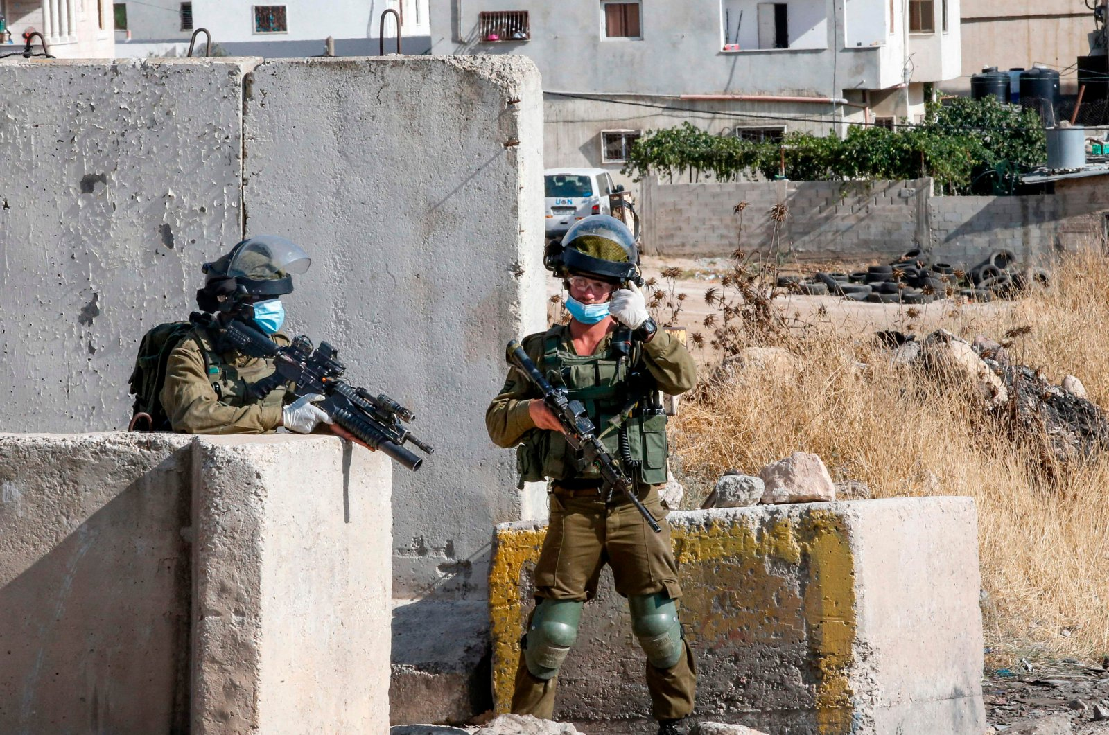 Mask-clad Israeli soldiers stand guard at a checkpoint at the main entrance of al-Fawwar camp for Palestinian refugees, south of Hebron in the occupied West Bank, July 9, 2020. (AFP Photo)
