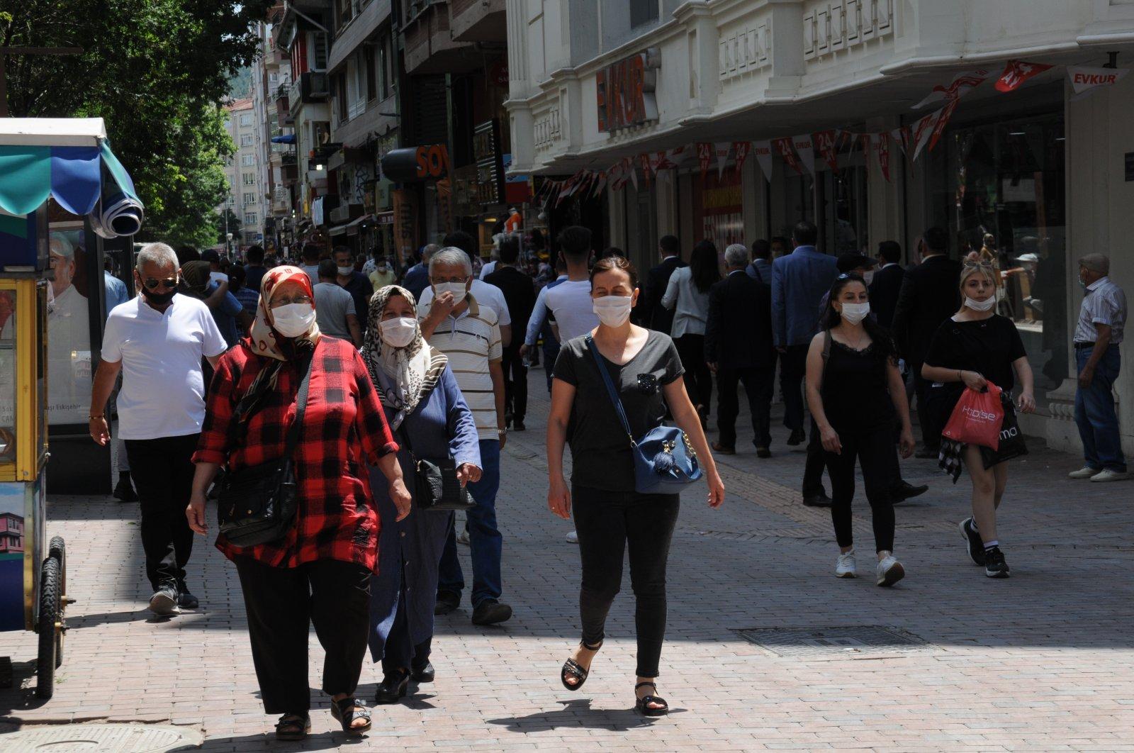People wearing masks against the coronavirus walk on the street, in Eskişehir, Turkey, July 14, 2020. (IHA Photo)