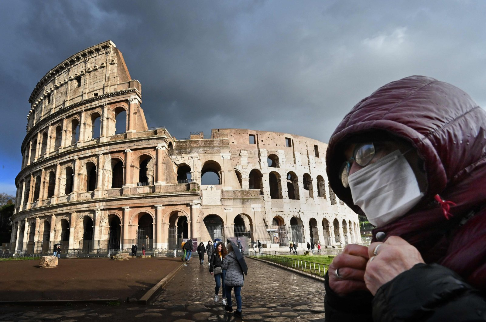 A man wearing a protective mask passes by the Coliseum monument in Rome amid fear of the Covid-19 pandemic, March 07, 2020. (AFP)