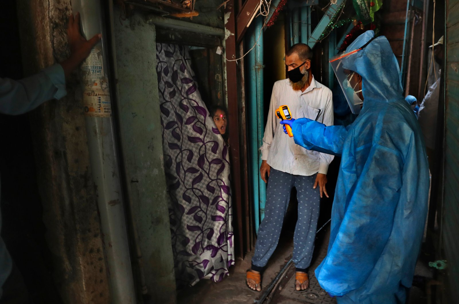 A doctor checks the temperature of a girl in Dharavi, one of Asia's largest slums, during lockdown to prevent the spread of the coronavirus in Mumbai, India. Monday, April 13, 2020. (AP Photo)