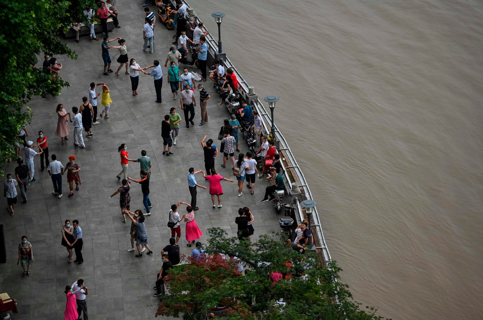 People dance next to the Yangtze in Wuhan, central Hubei province, China, July 14, 2020.  (AFP Photo)